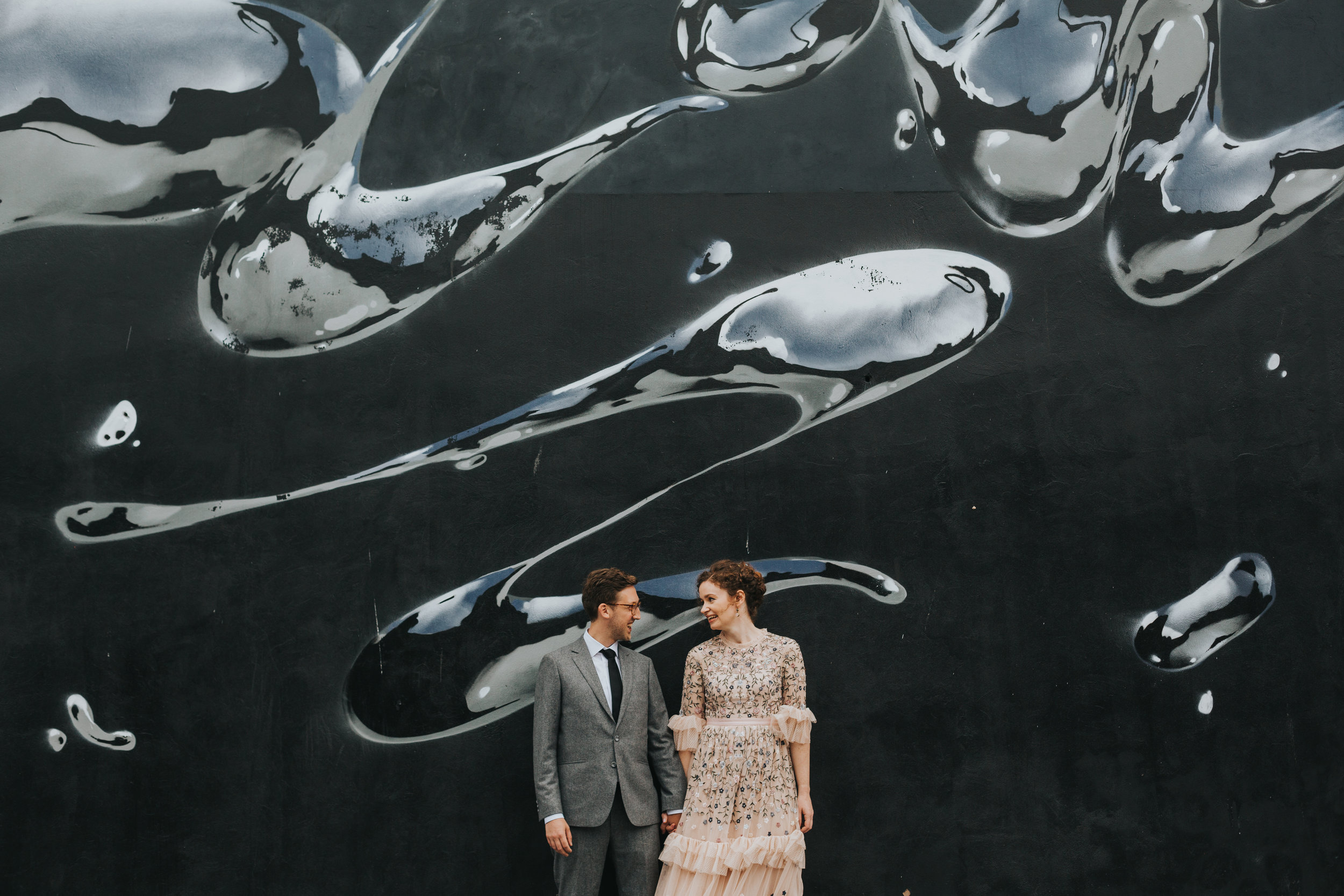 Bride and Groom in front of black and sliver metallic liquid mural.