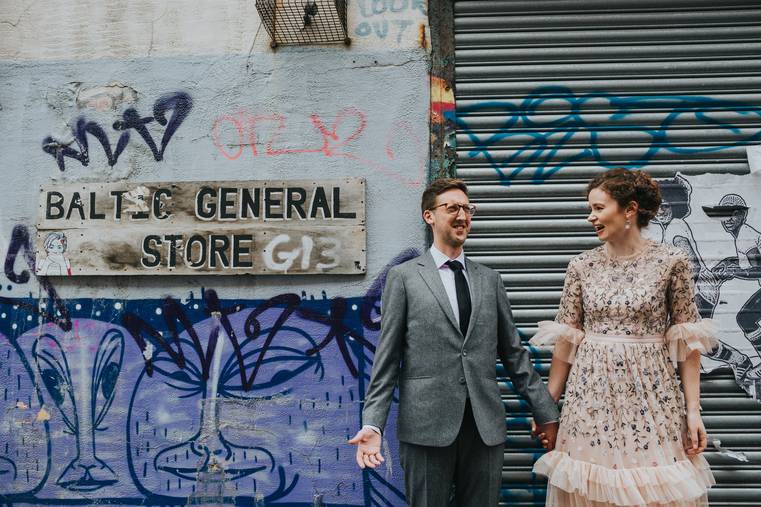 Bride and Groom laugh together besides Baltic General Store Sign.