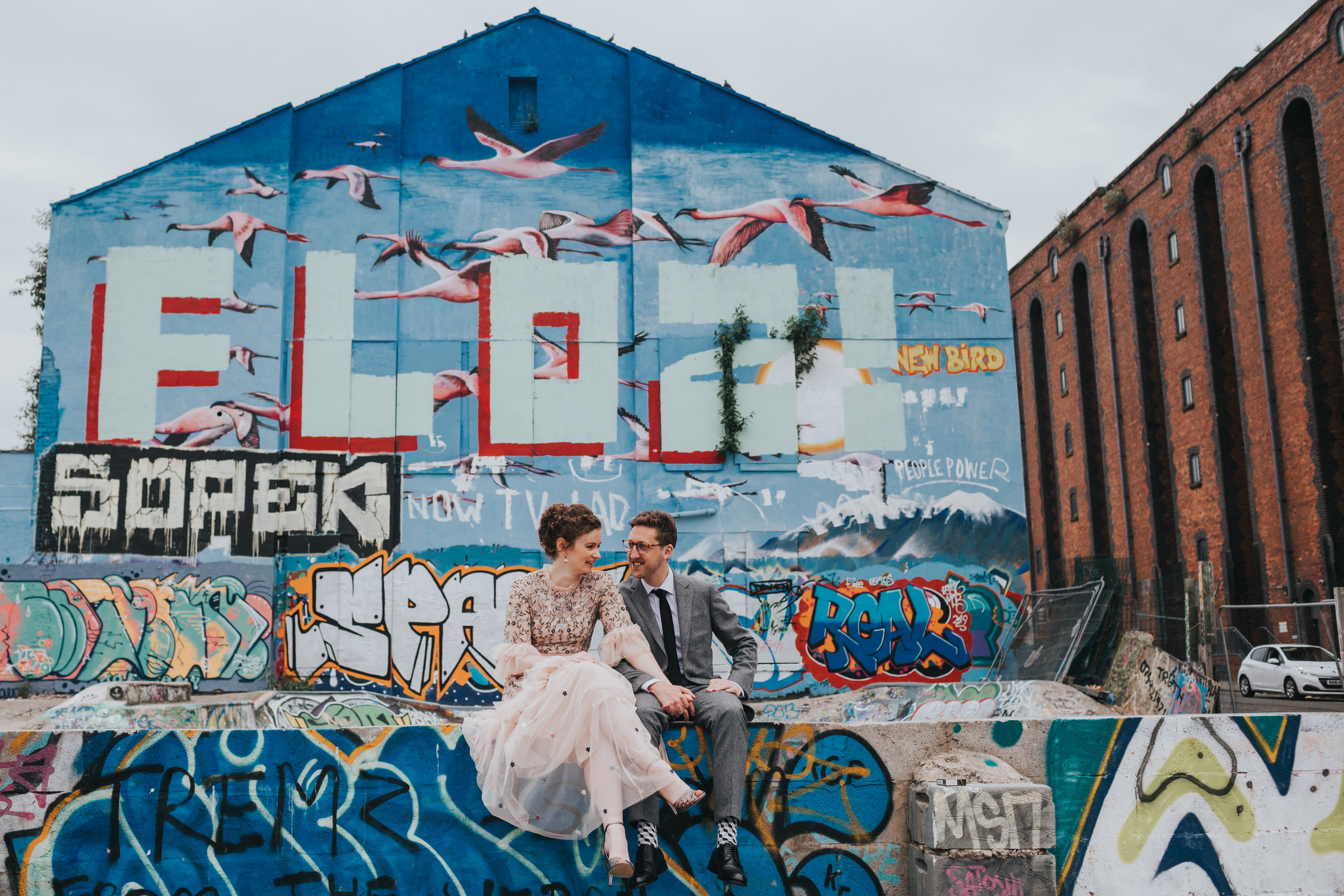 Bride and Groom sit in front of a blue and pink mural of a flock of flying flamingos.
