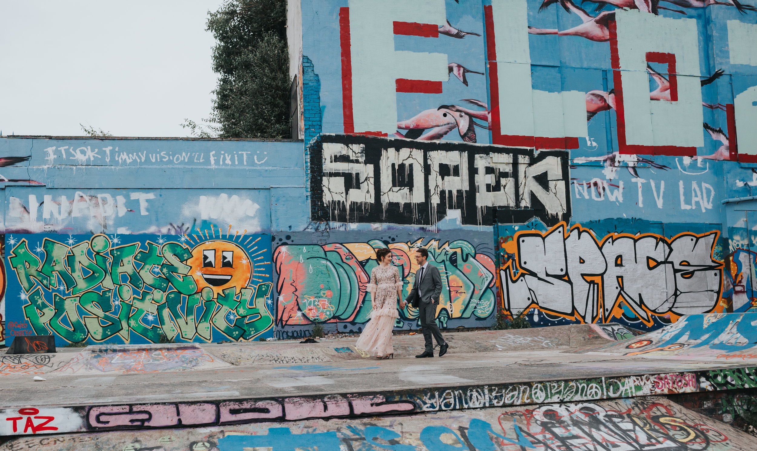 Bride and Groom walk through skate park together.