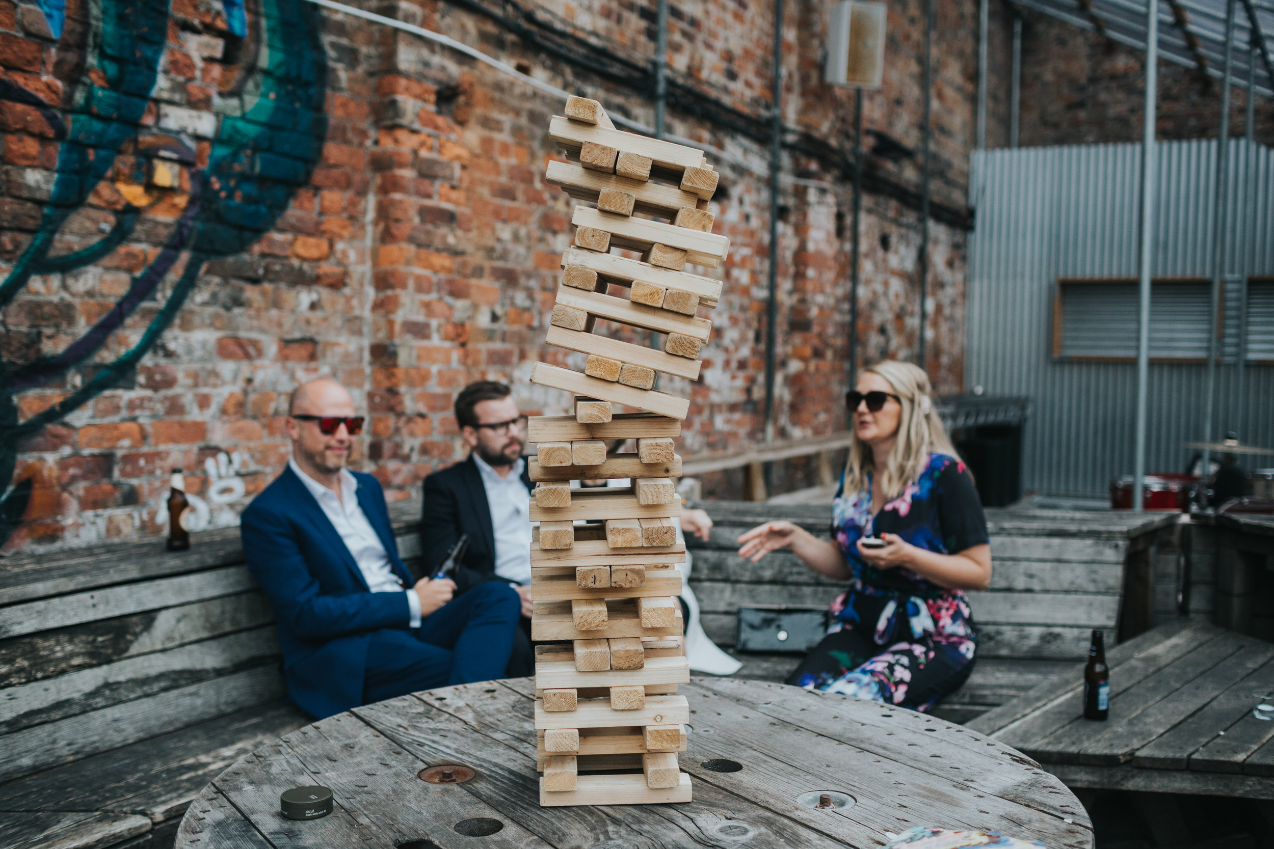 Guests sit nervously next to a precariously stacked Jenga tower.