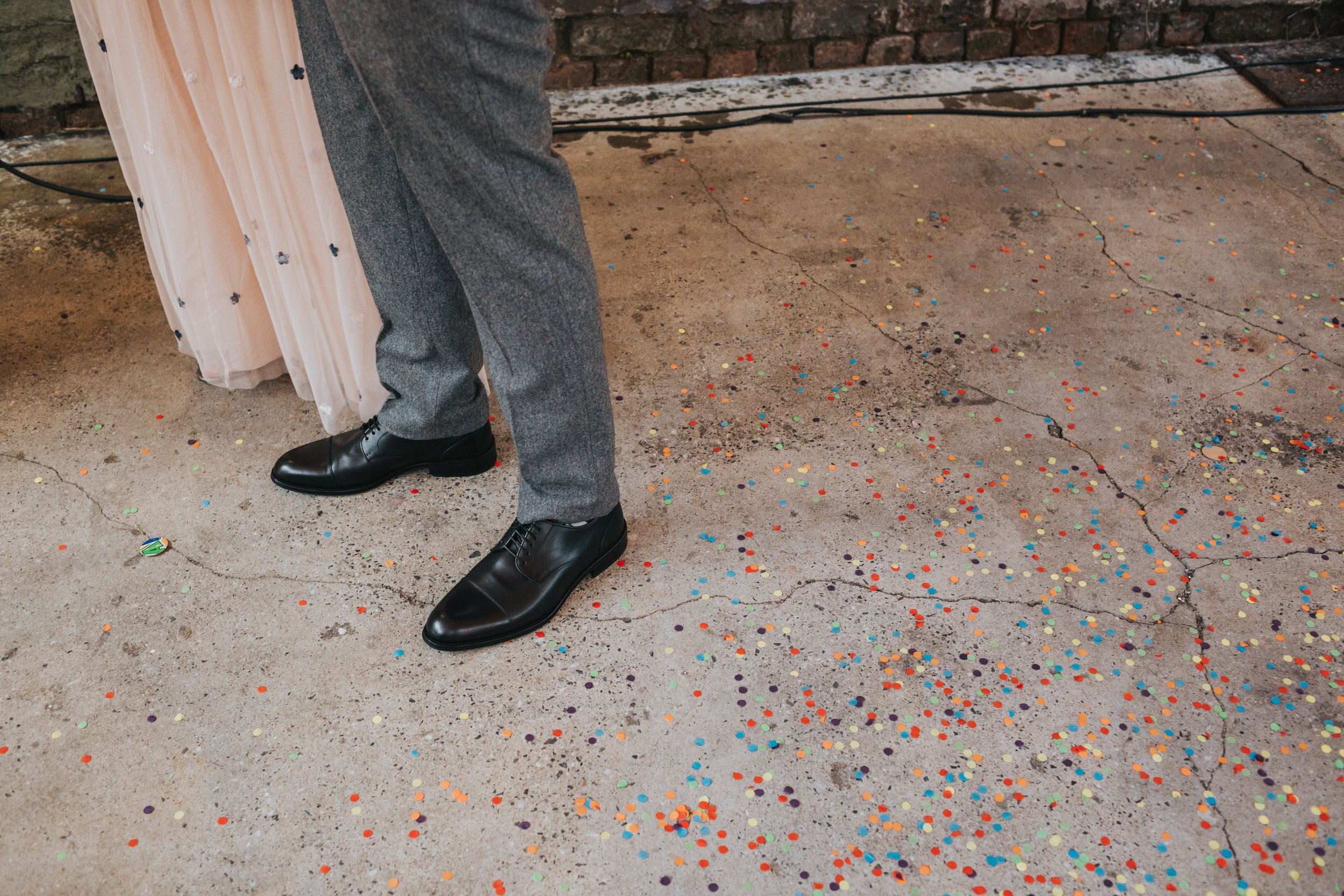 Bride and Grooms feet amongst colourful confetti.