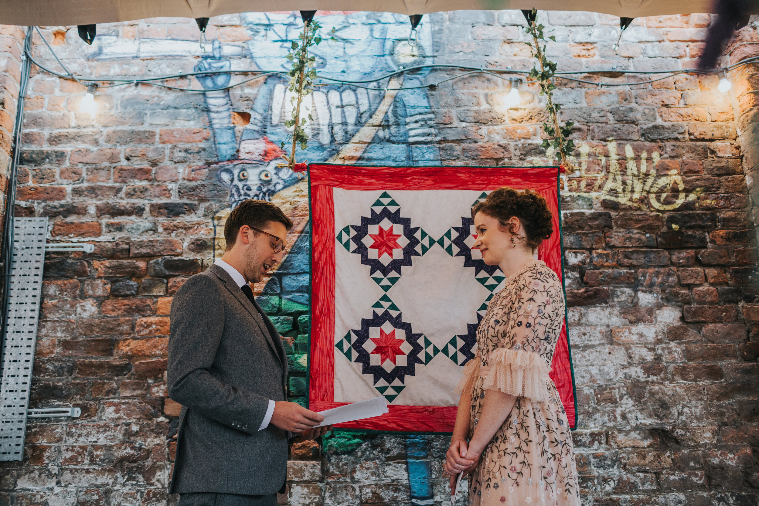 Bride and groom say their vows in front of a patch work blanket.