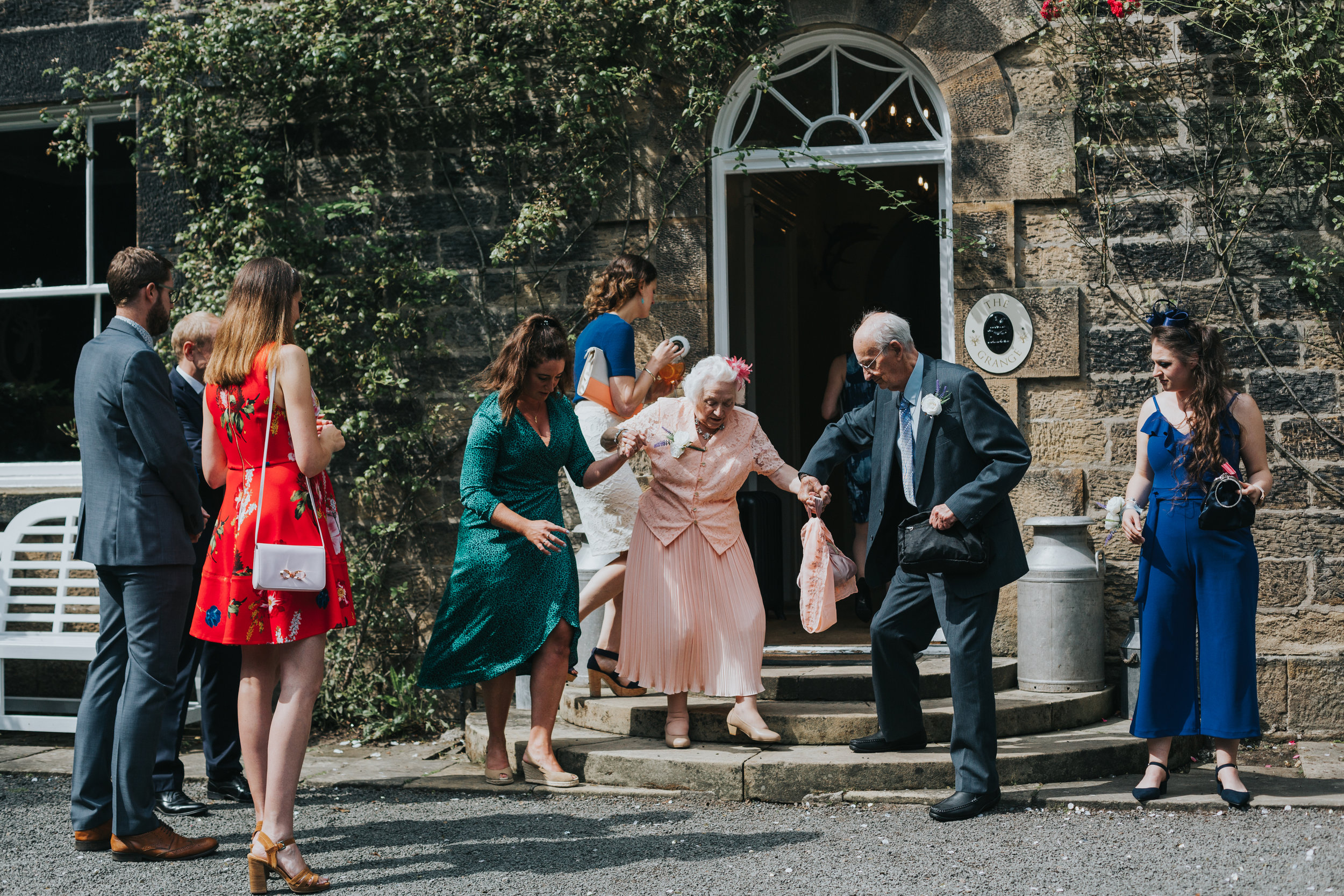 Guests help Grandma down the steps.