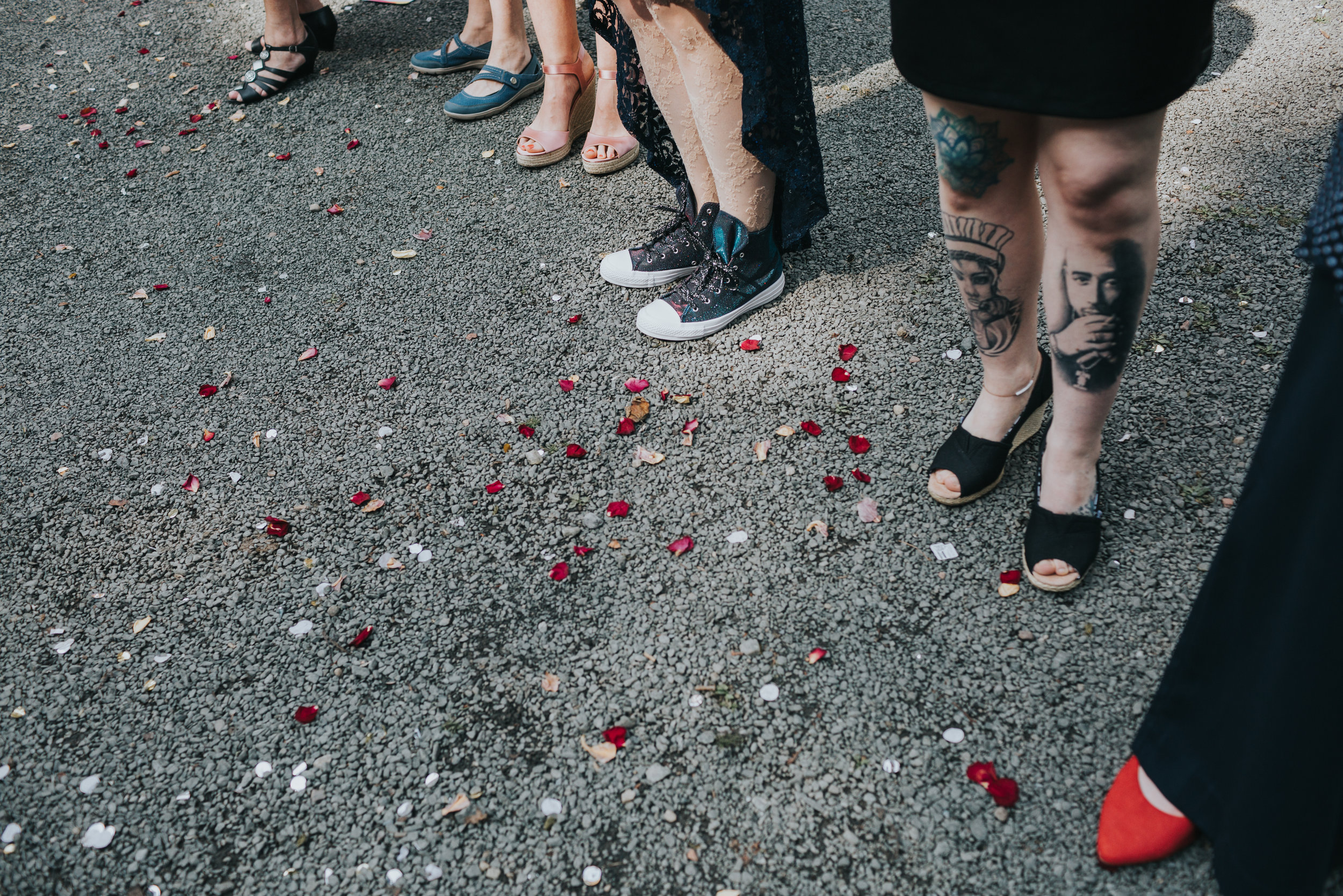 Natural petal confetti on the floor next to guests tattooed legs.