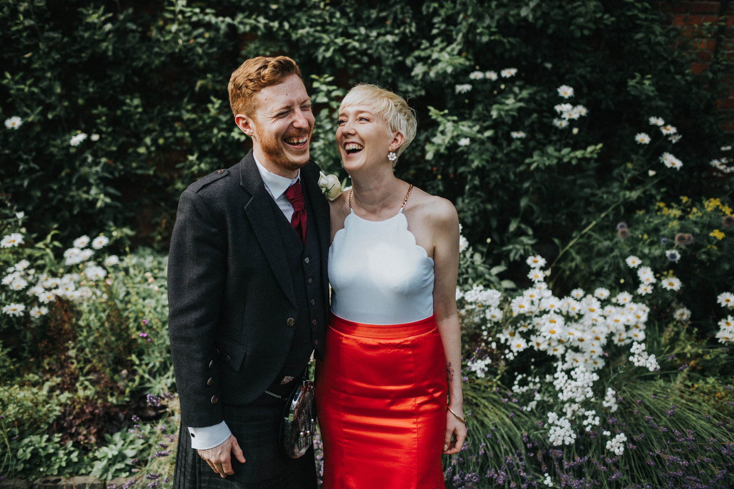 Untraditional bride and groom stand laughing on their chilled out wedding celebration.