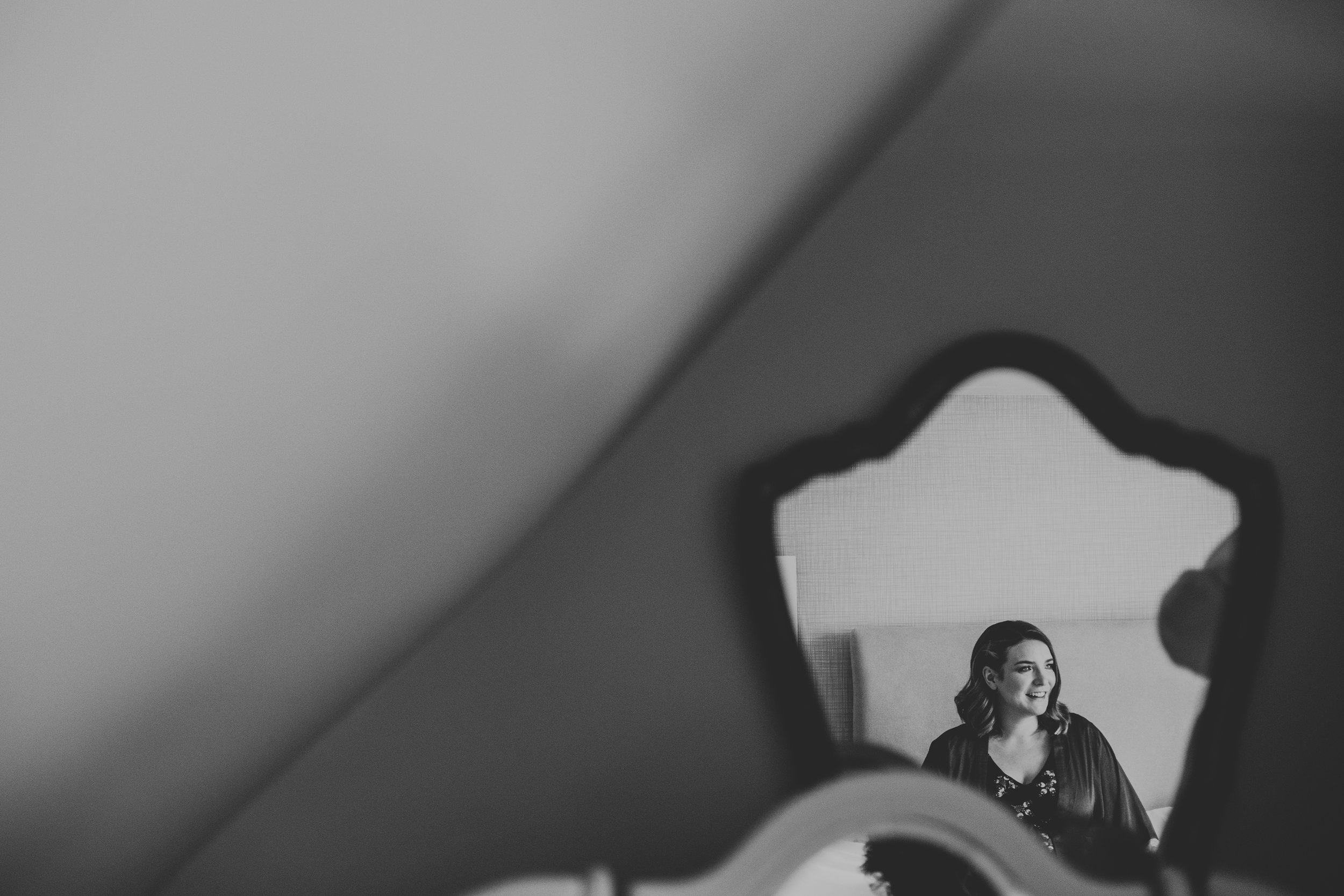 Reflection of bridesmaid in mirror. Photo in black and white.
