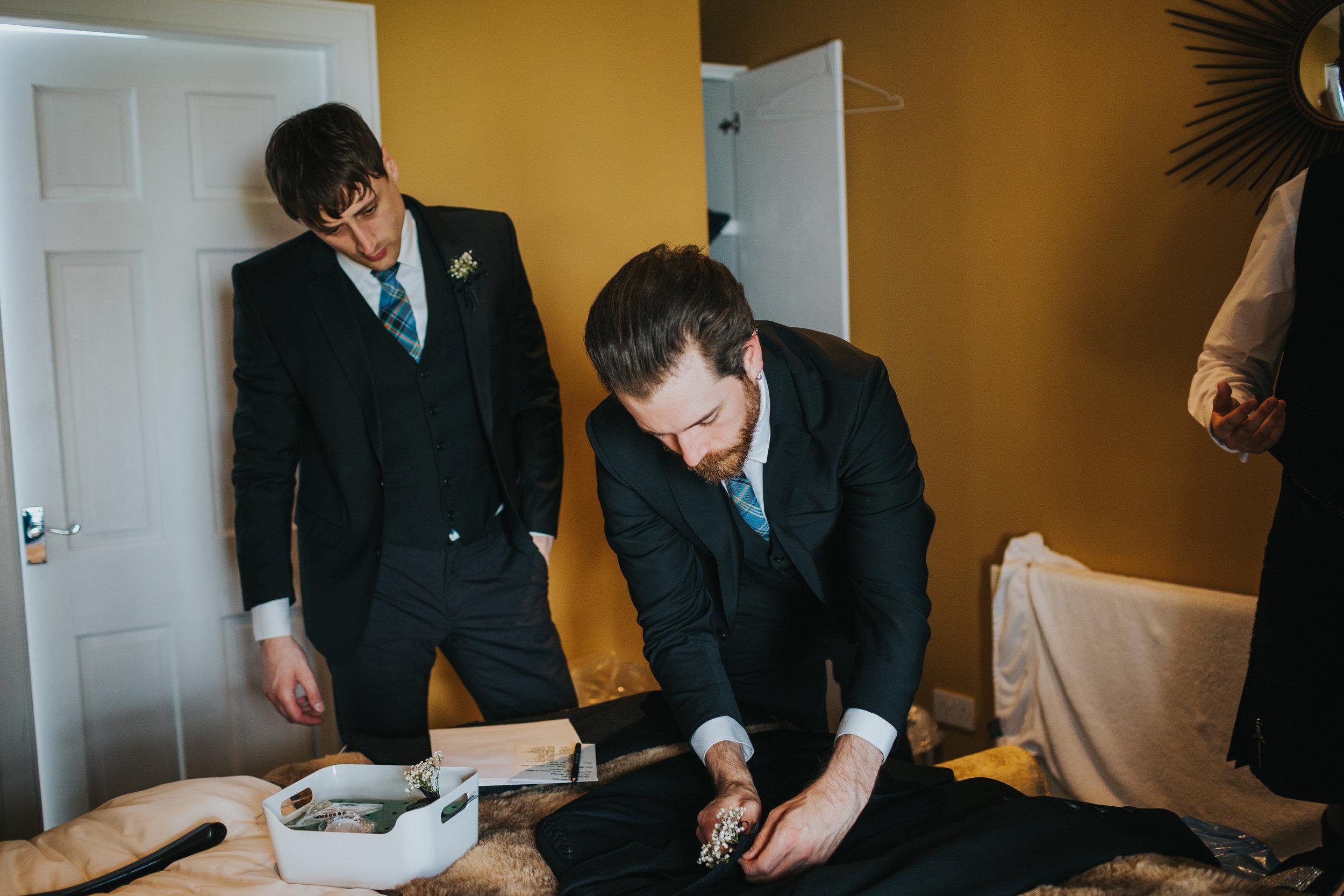 Groomsmen help prepare grooms suit.
