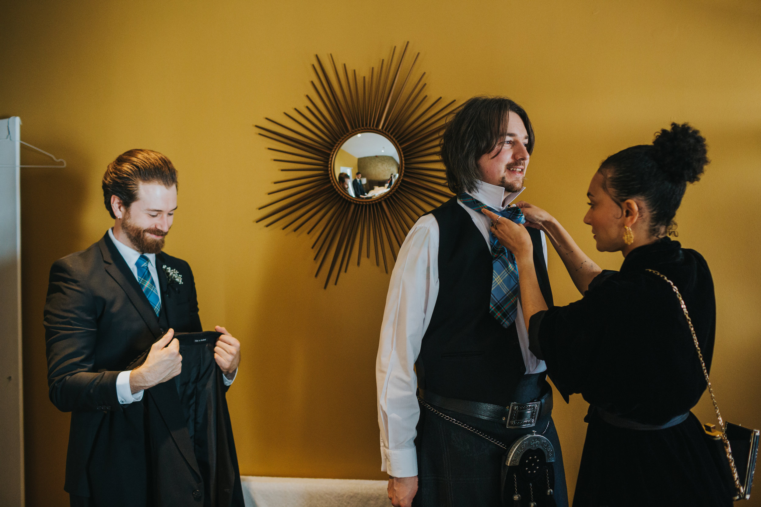 wedding guest helps Groom get dressed.