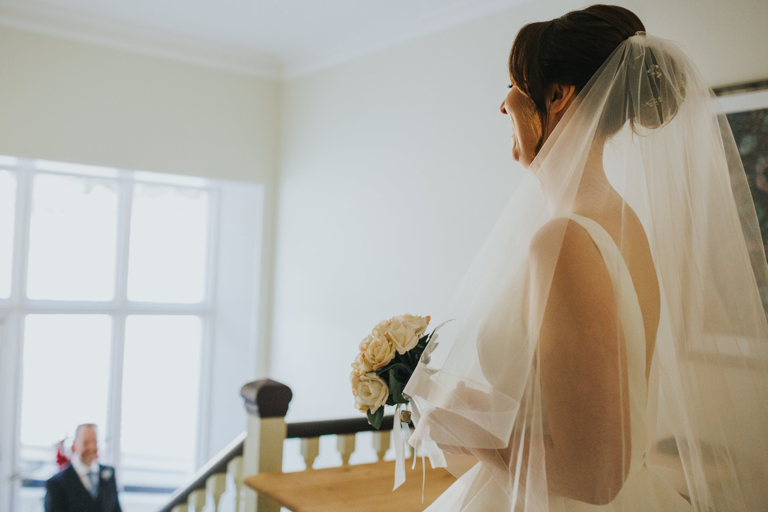 Bride stands at the top of the stairs smiling.