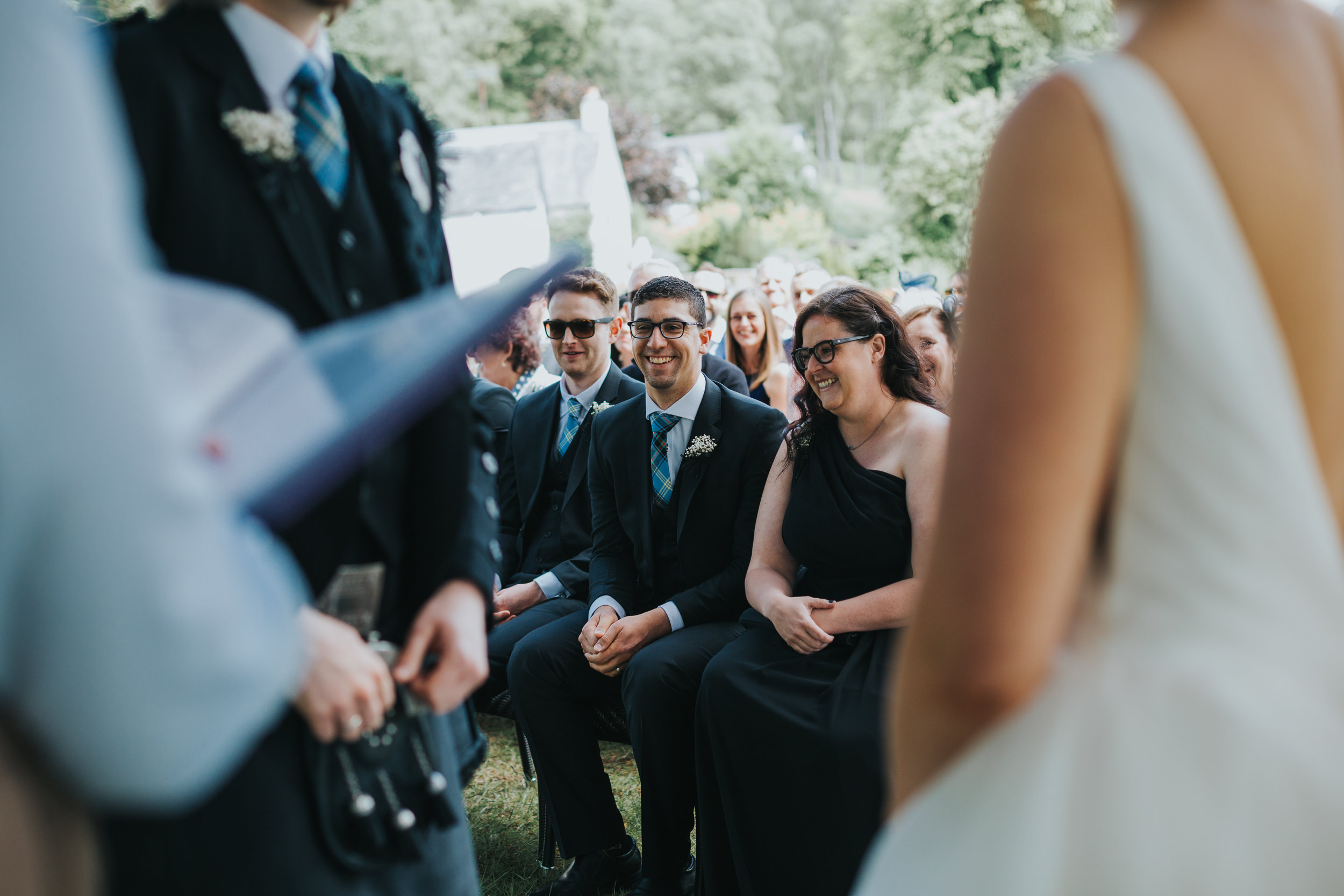 Groomsmen laugh at reading.
