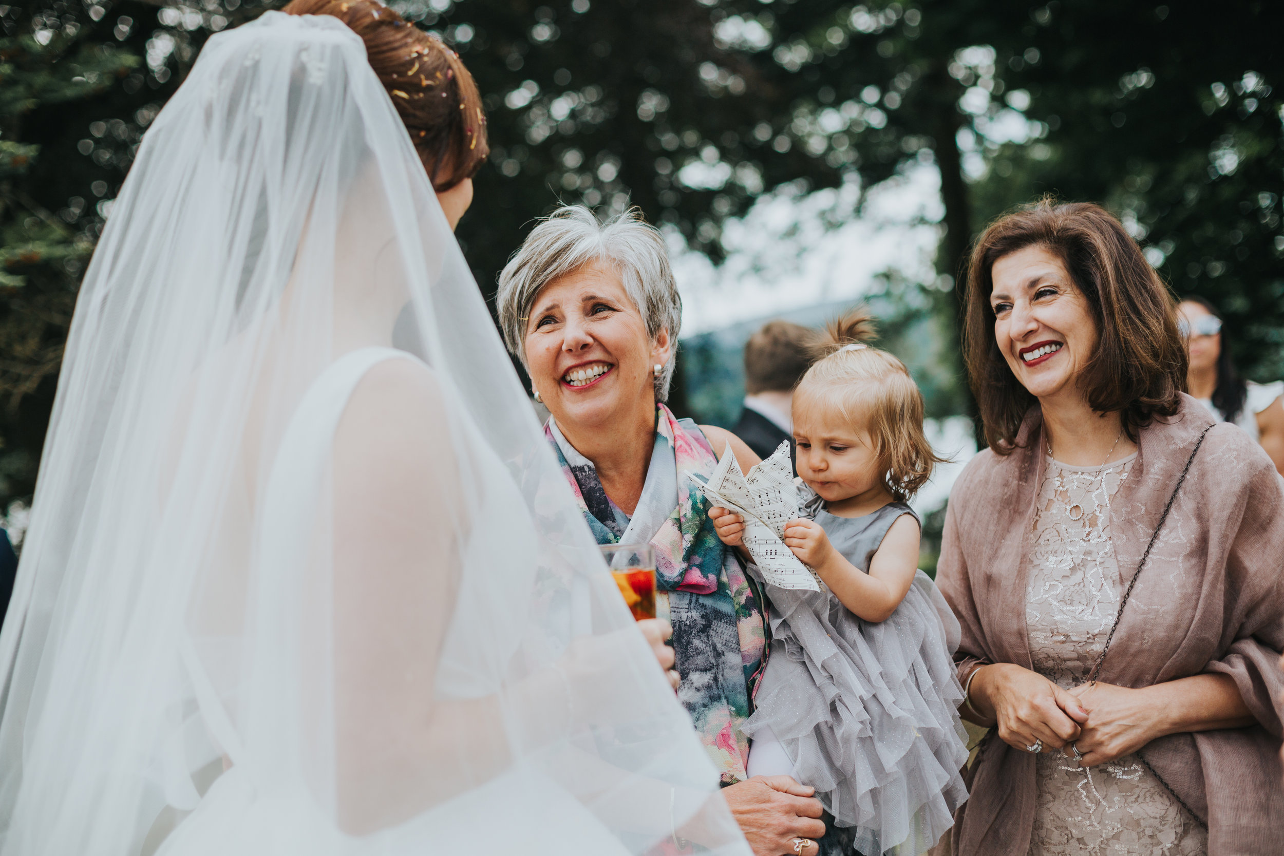Bride greets smiling wedding guests holding a baby.