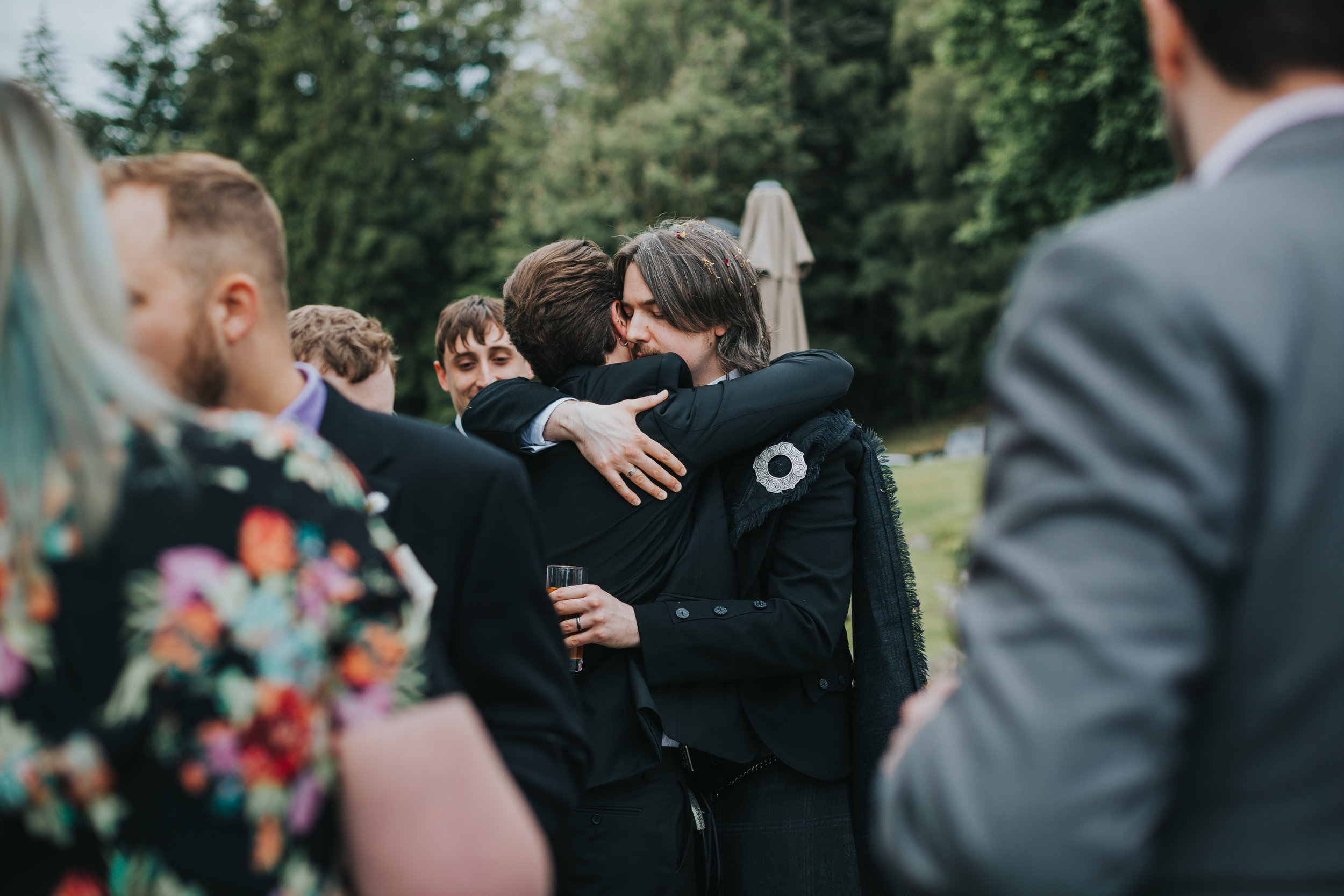 Groom hugs wedding guest.