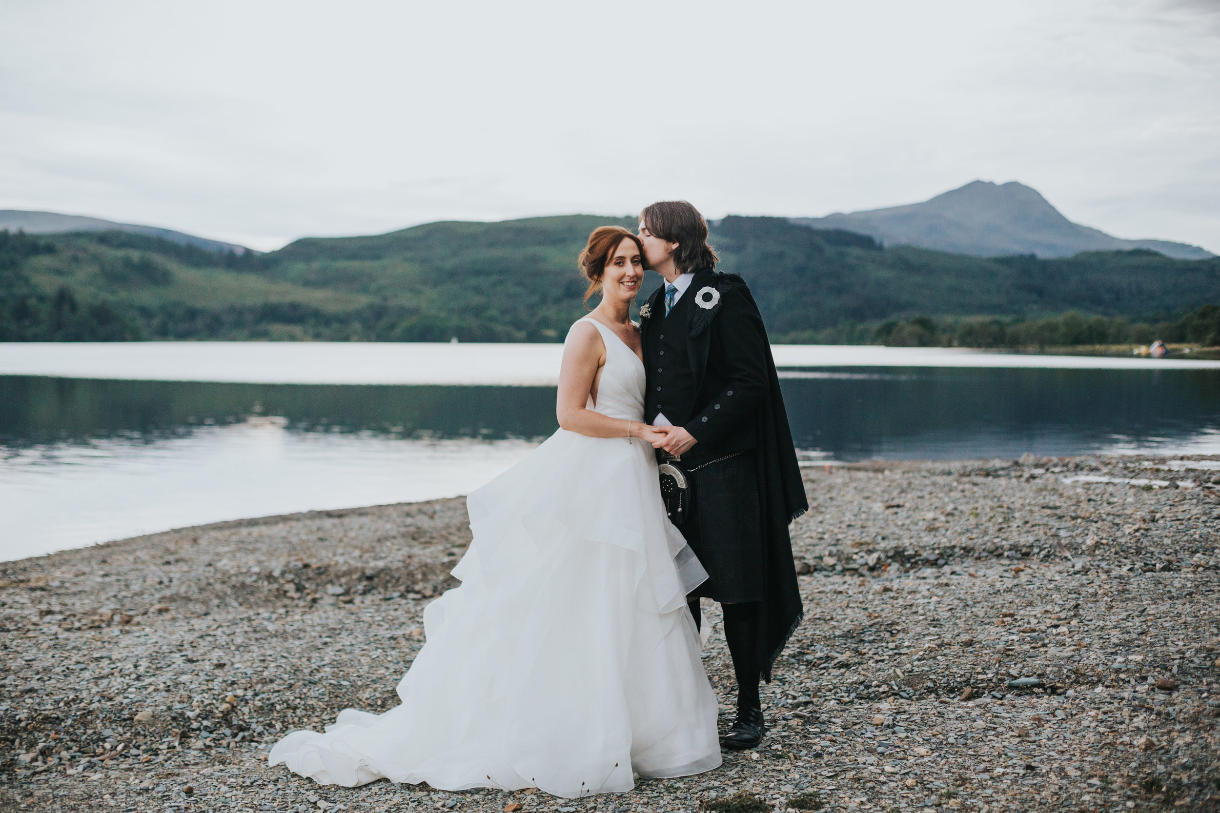 Bride and groom stand on beach of Loch Ard.