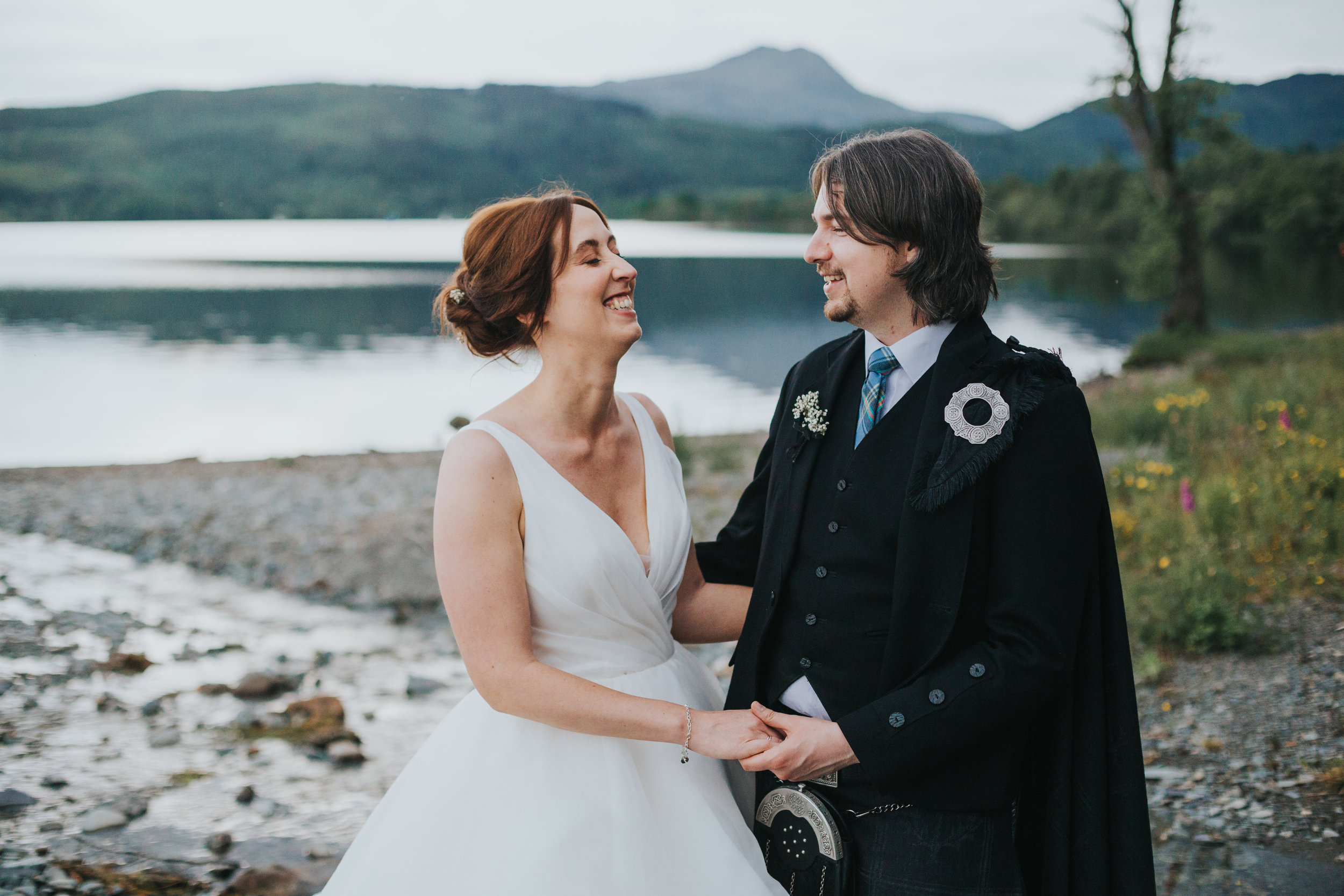 Bride and Groom laughing in front of Loch Ard.