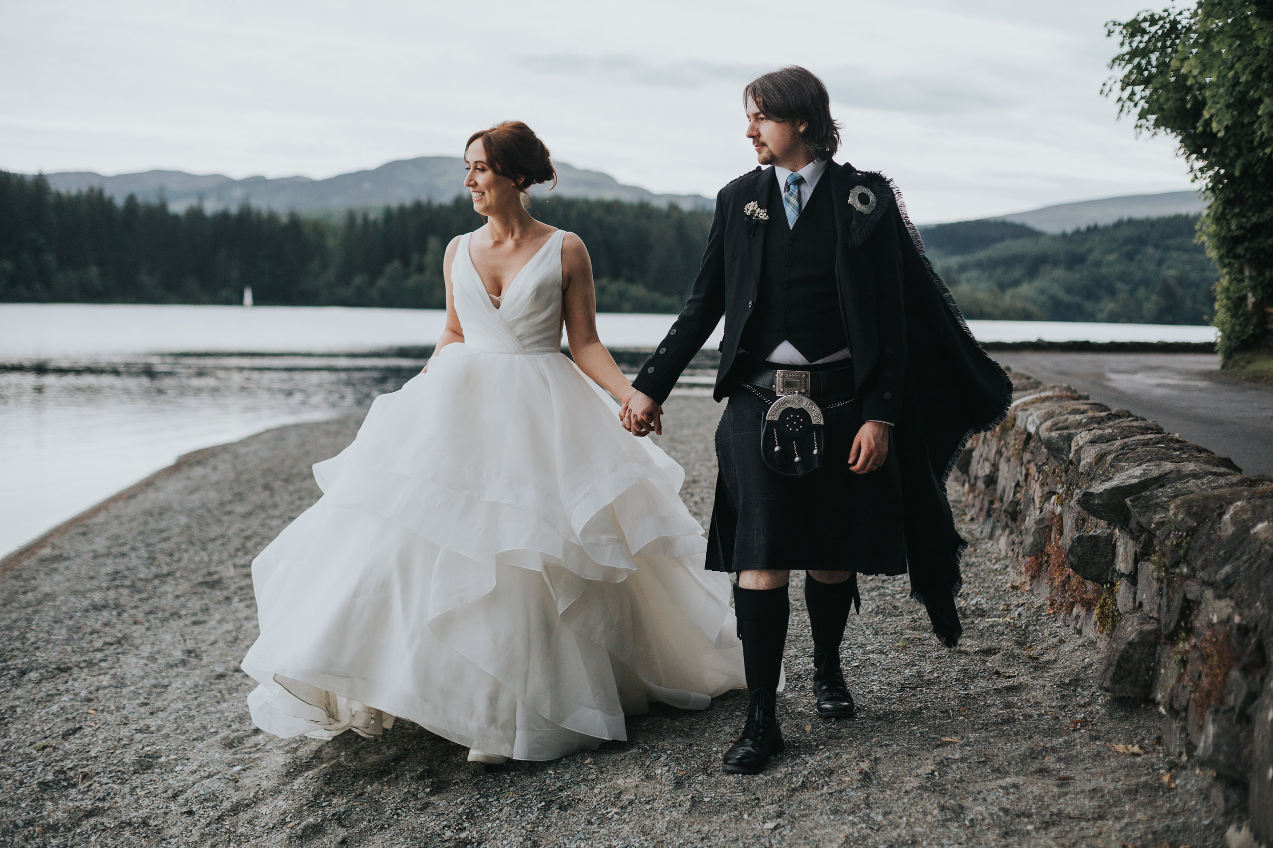Bride and Kilted Groom walk together along the pebbled beach at Loch Ard, Scotland.
