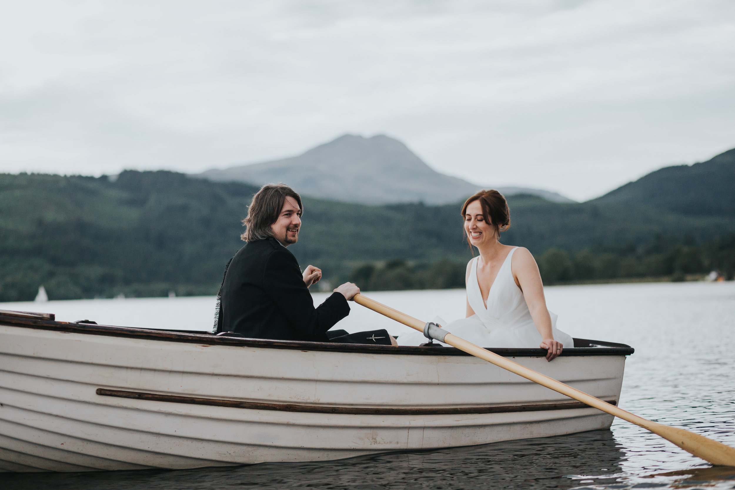 Bride and Groom laugh together in rowing boat on Loch Ard on their Wedding day.