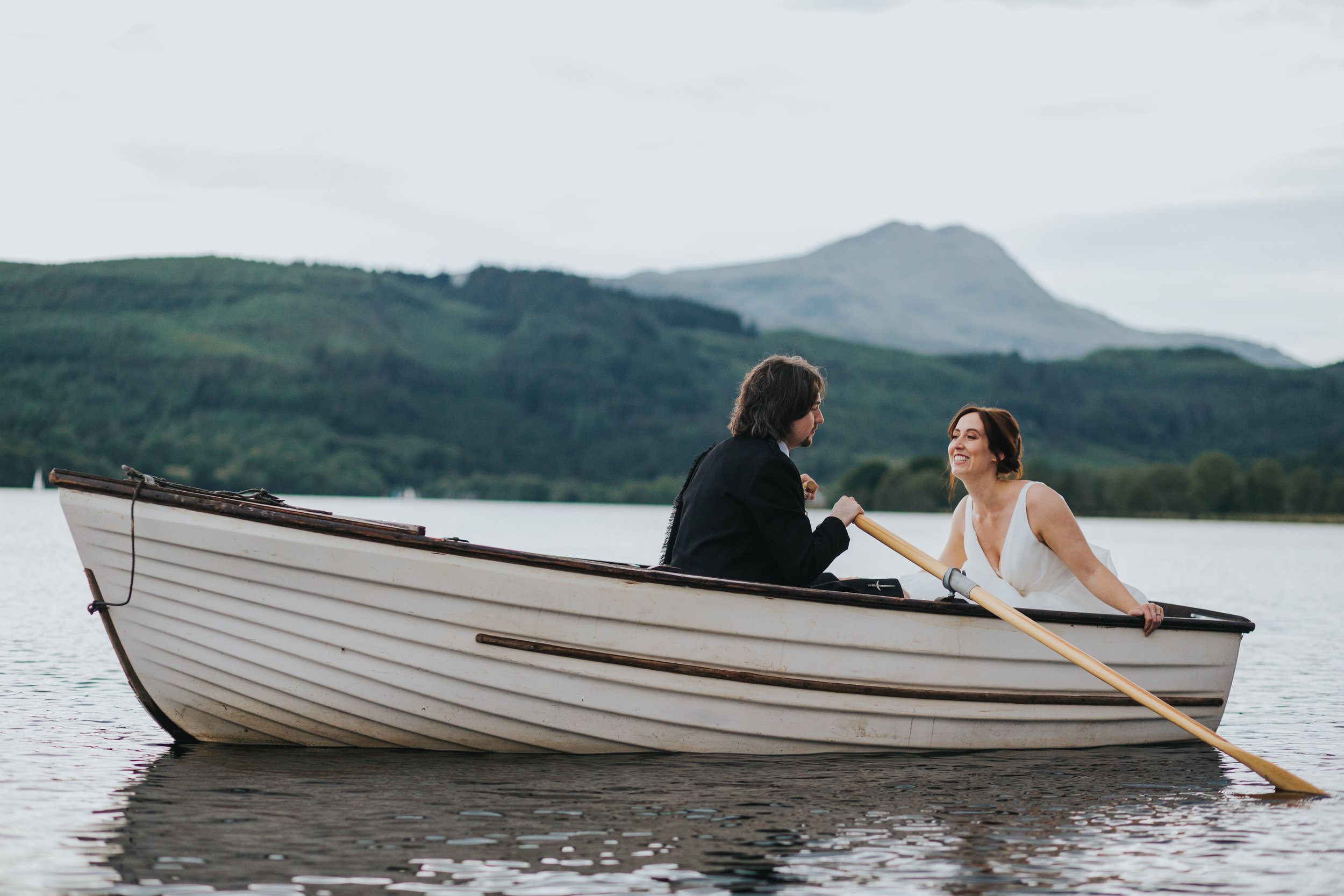 Bride leans towards her groom as her rows them across Loch Ard on their wedding day.