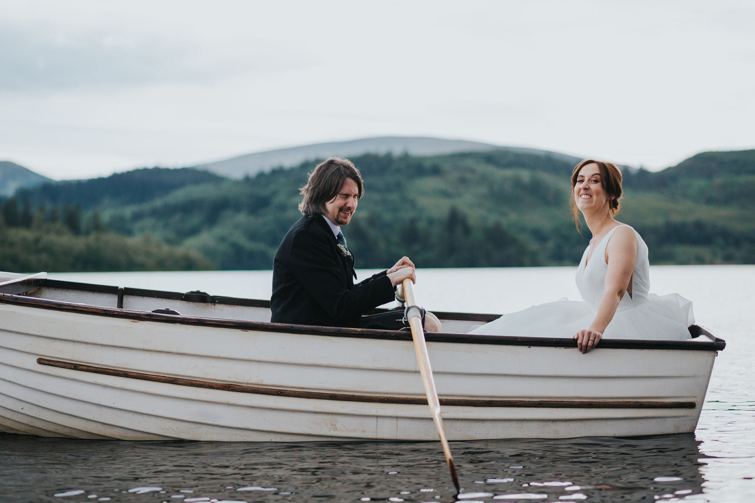 Bride pulls a funny face while groom laugh in rowing boat on Loch Ard.
