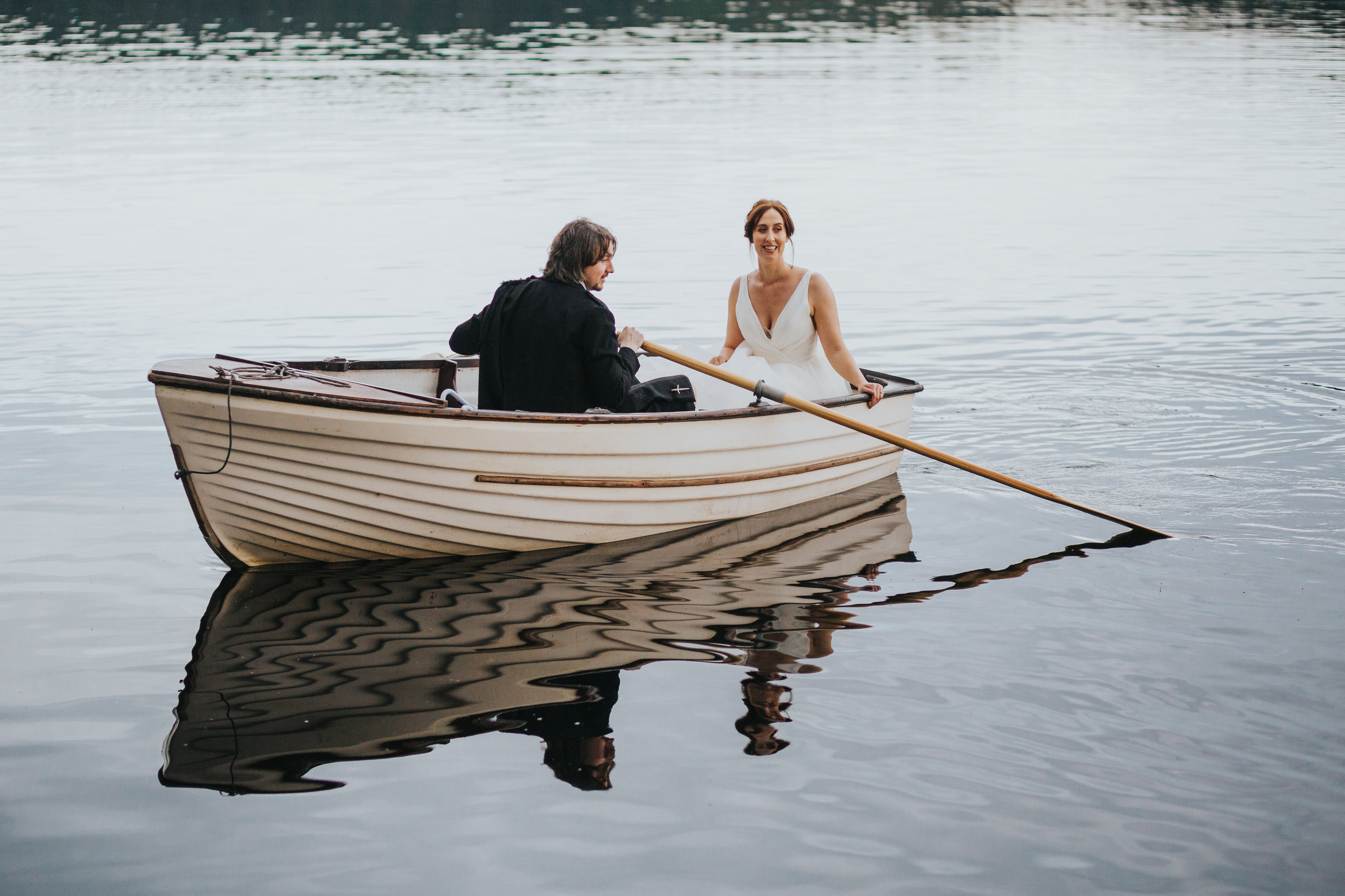 Bride and groom reflected in the water on Loch Ard.