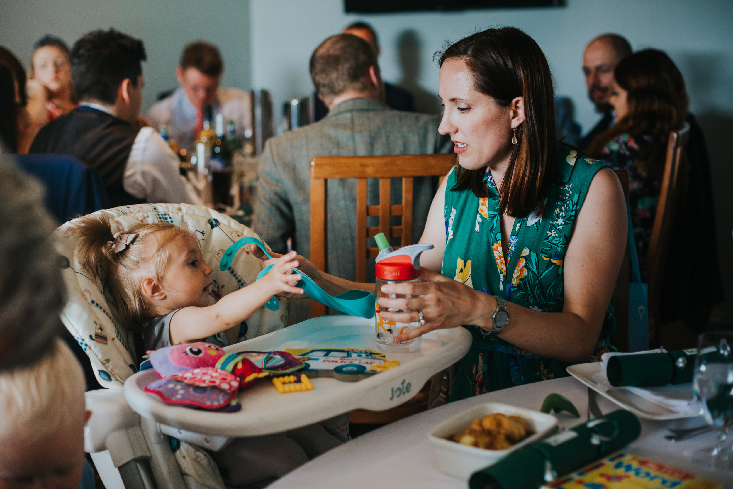 Wedding guest feeds her baby girl.