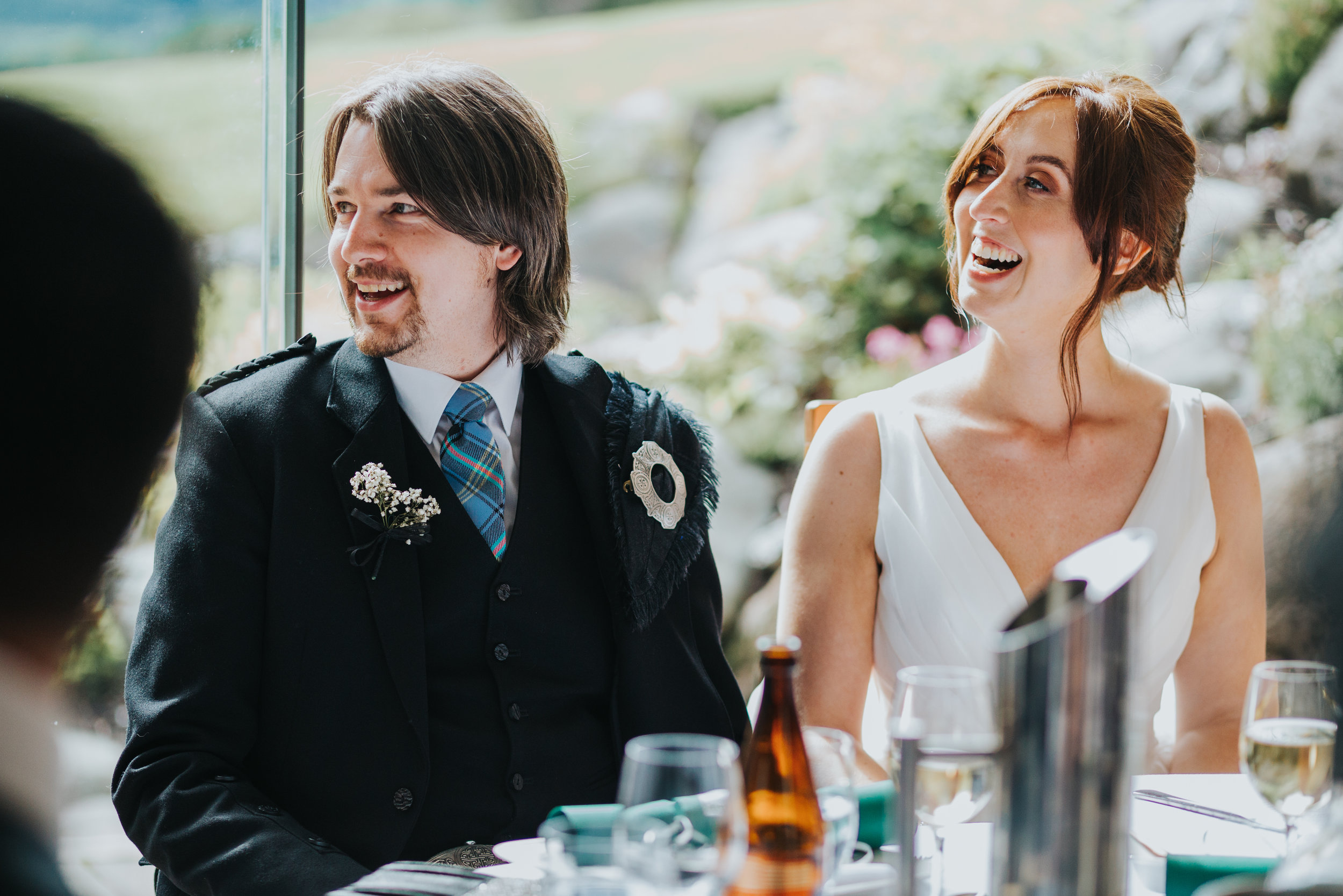 Bride and Groom laugh at speech.