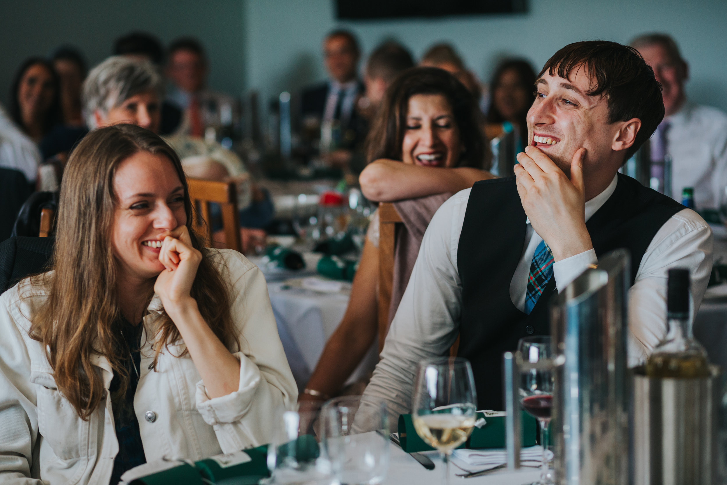 Wedding guests laugh at the grooms speech.