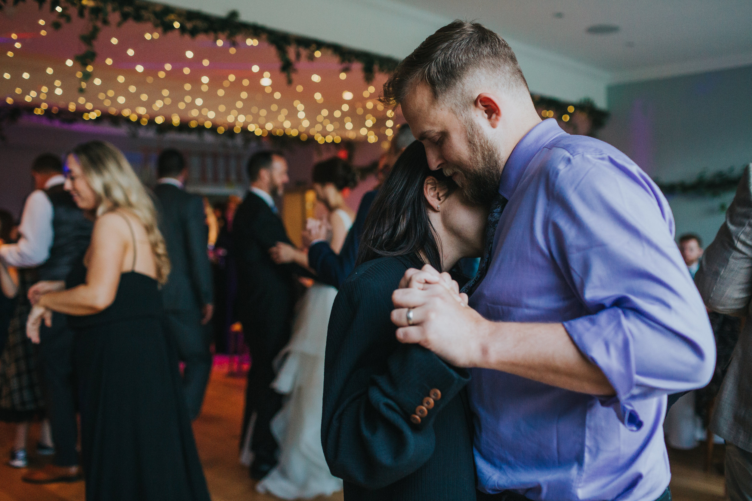 Wedding guests have a romantic moment on the dance floor.
