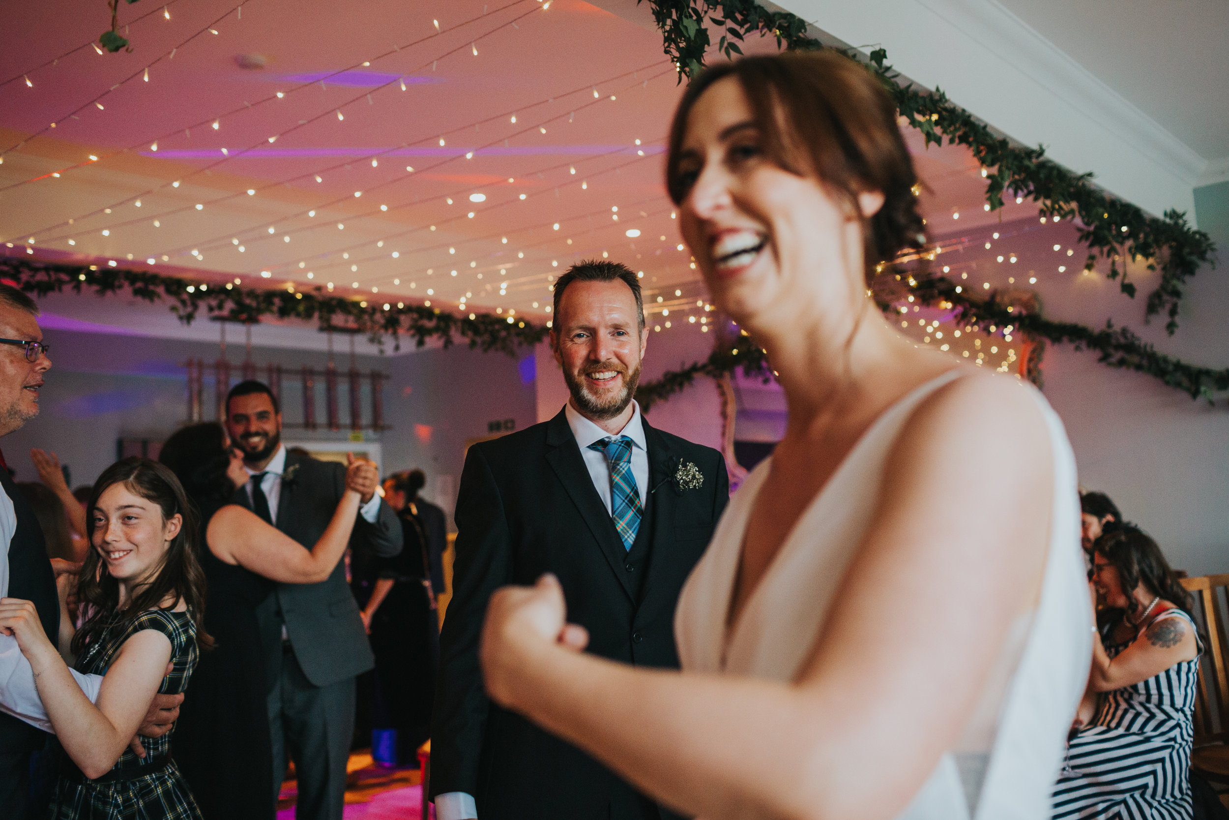 Bride laughing while dancing with her brother.