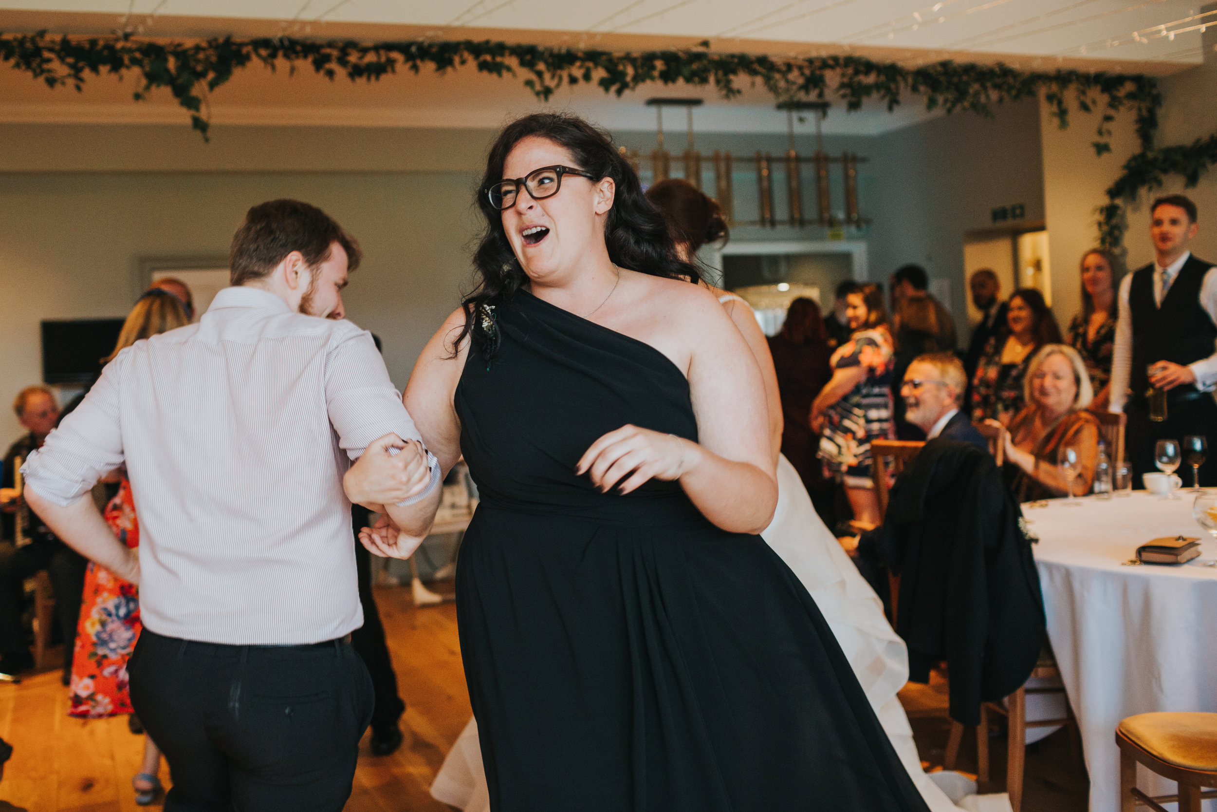 Wedding guest pulls funny face while dancing.