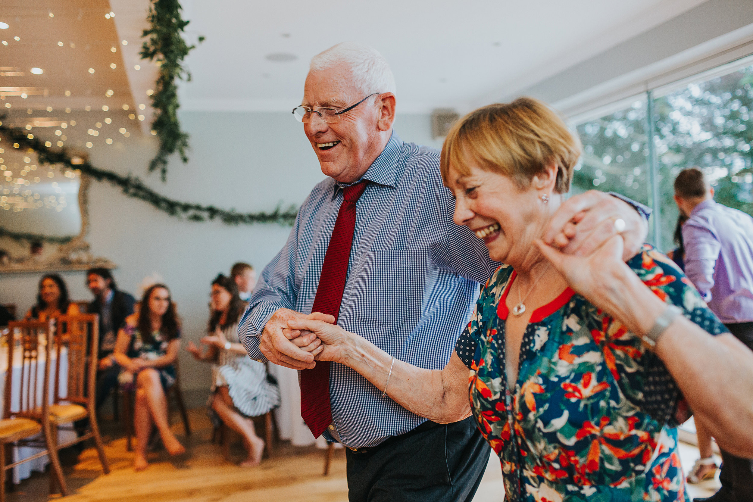 Older couple laughing and dancing together.