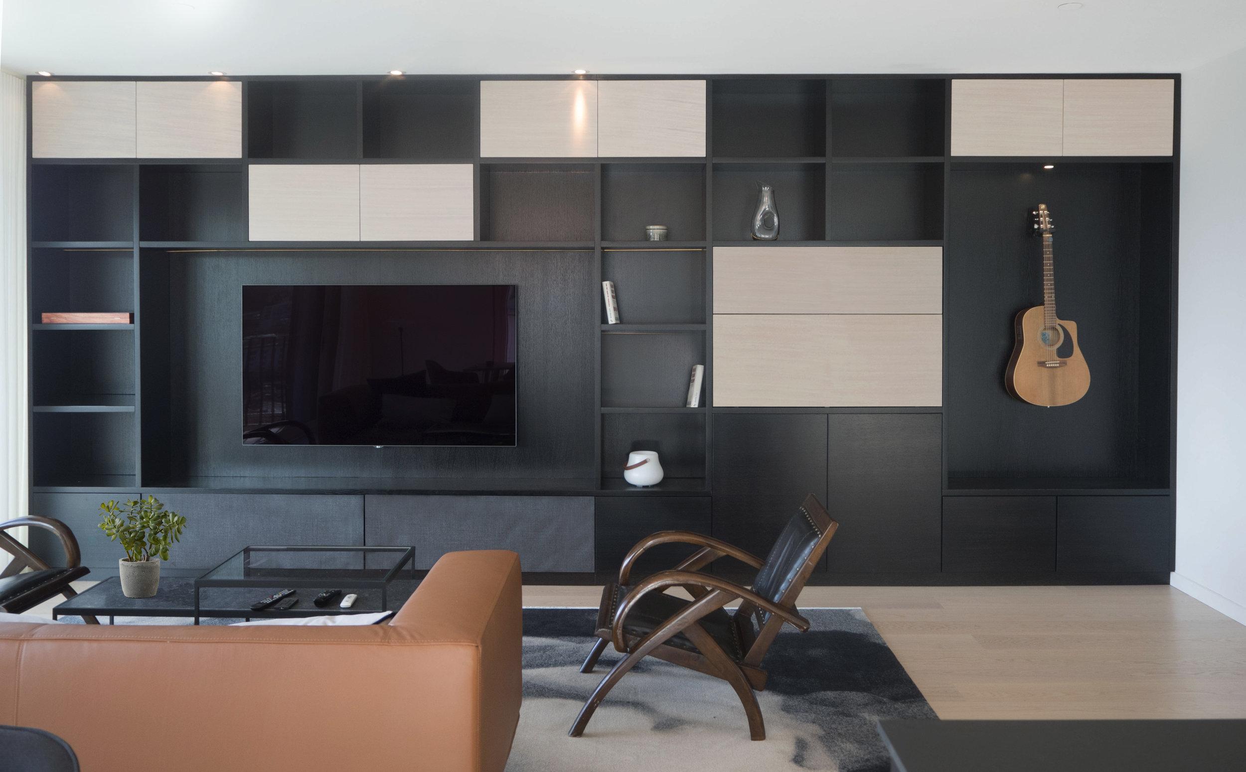 Et av leilighetens smykker er bokhyllen som er skreddersydd for å romme elementer etter kundens ønsker.