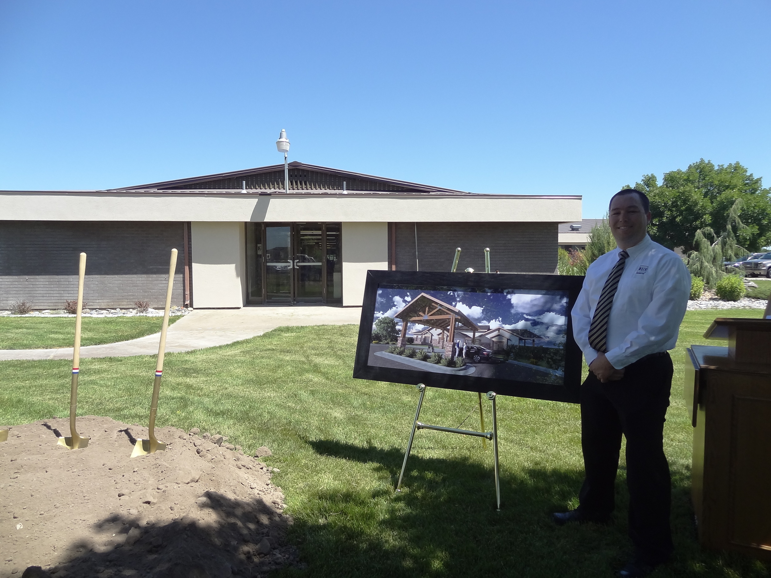 DEIV Architecture's President, David Clayton, AIA, standing in front of the rendering of how the facility will look upon completion.