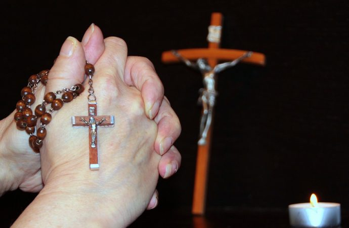 A woman prays the Rosary. (Credit: Max Pixel.)