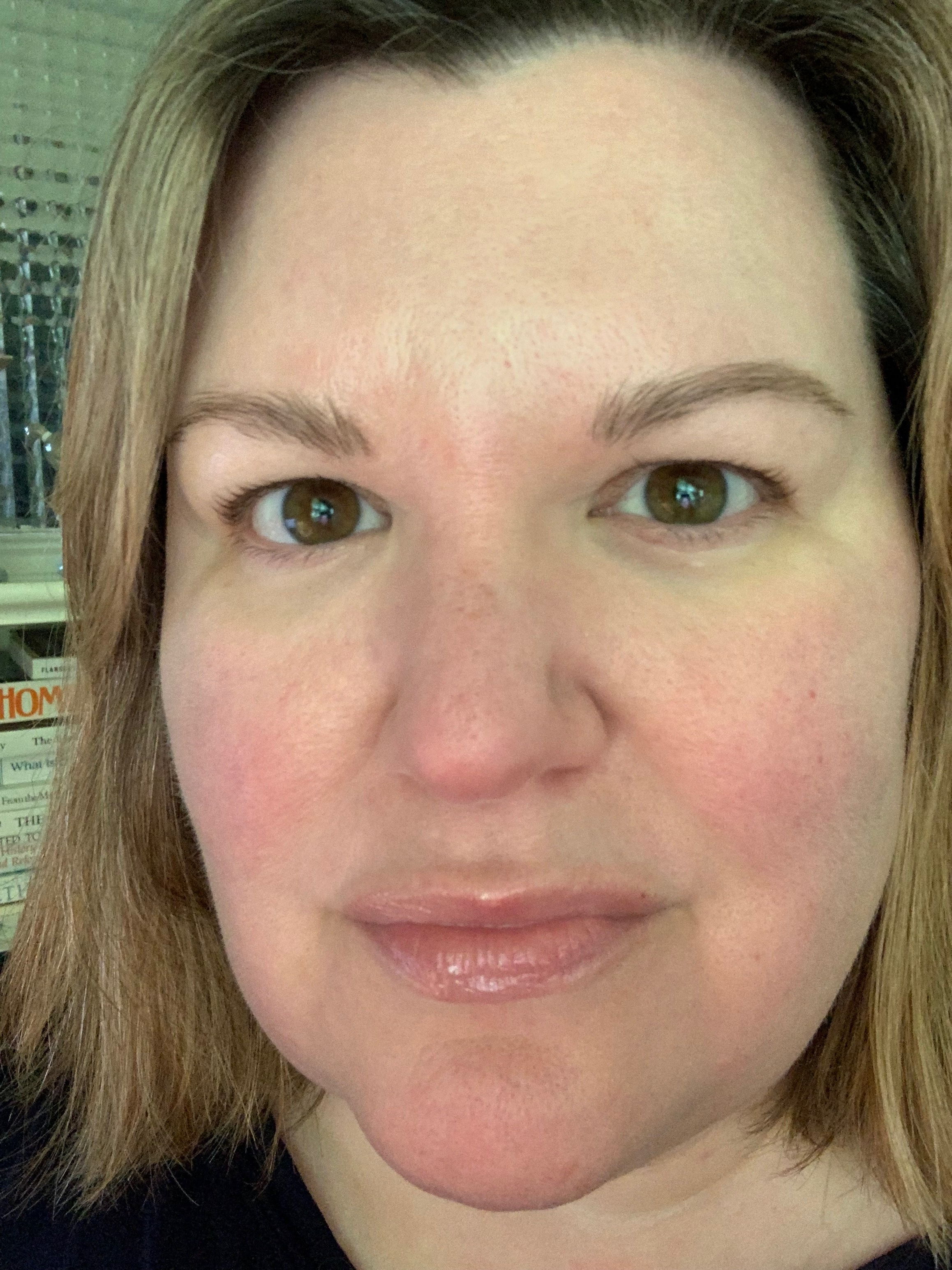 You can see the ever-present redness from the rosacea. I deal with redness the most. This photo also shows the second thing I deal with: crazy hair texture that is fine, prolific, straight, and wavy. Thank you to my hysterectomy! I just have on my morning routine and lip balm. #nofilter  And a shout-out to doing a skincare post with a book on Homiletics (preaching) in the background. That is truly how I move through life!