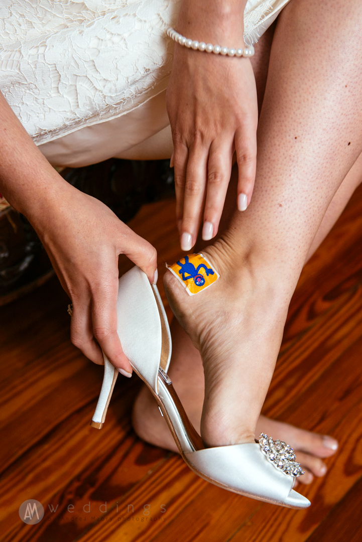 """Corbie's """"something blue"""" ended up being this Elmo band-aid! Here, she pulls on her shoes at the Maison Perrier before getting married on a New Orleans streetcar."""
