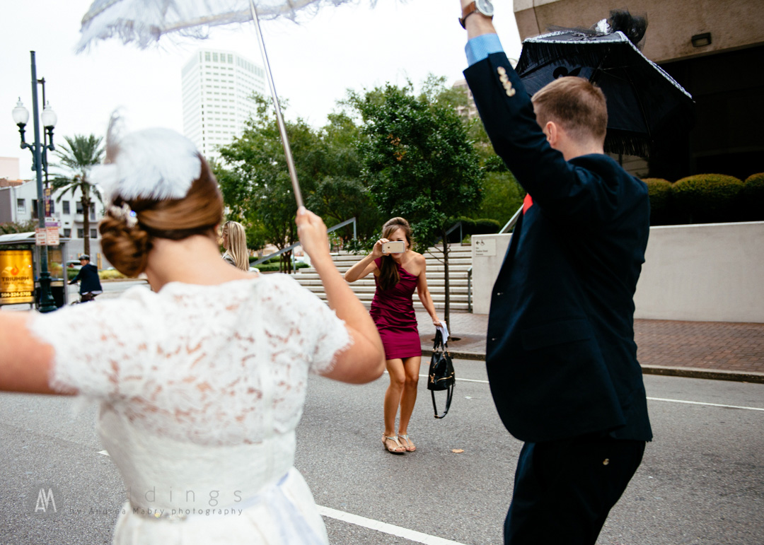 The bride's sister photographs the newlywed couple during their second line down Carondelet.