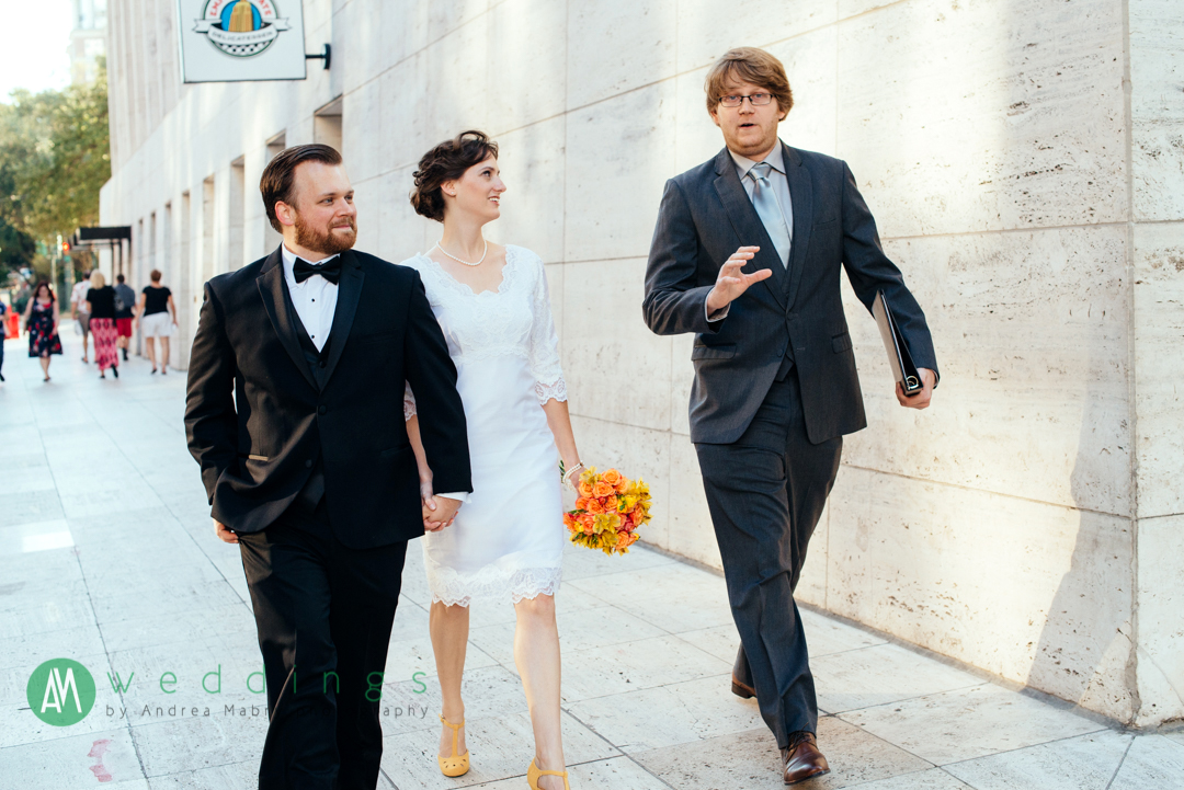 Georgia and Bob walk with their officiant and longtime friend to catch a ride to the New Orleans Wax Museum.