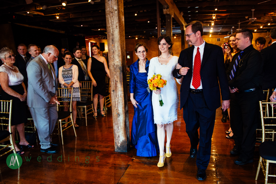 The bride's parents walk her down the aisle during the wedding ceremony at the New Orleans Wax Museum.