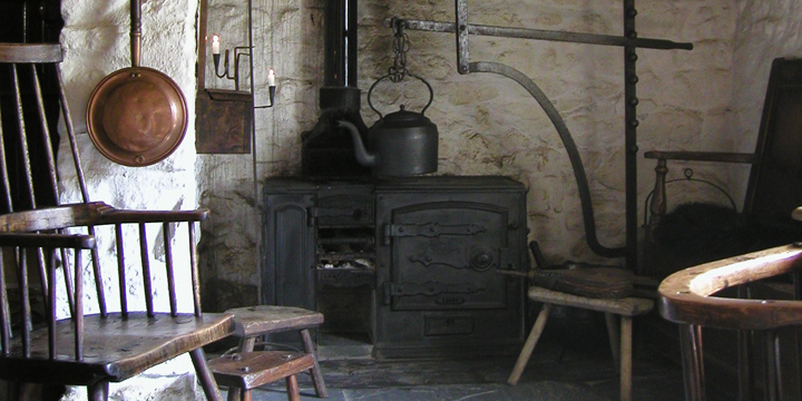Original kitchen containing an impressive inglenook fireplace with Welsh Country antiques set against the lime-washed walls.