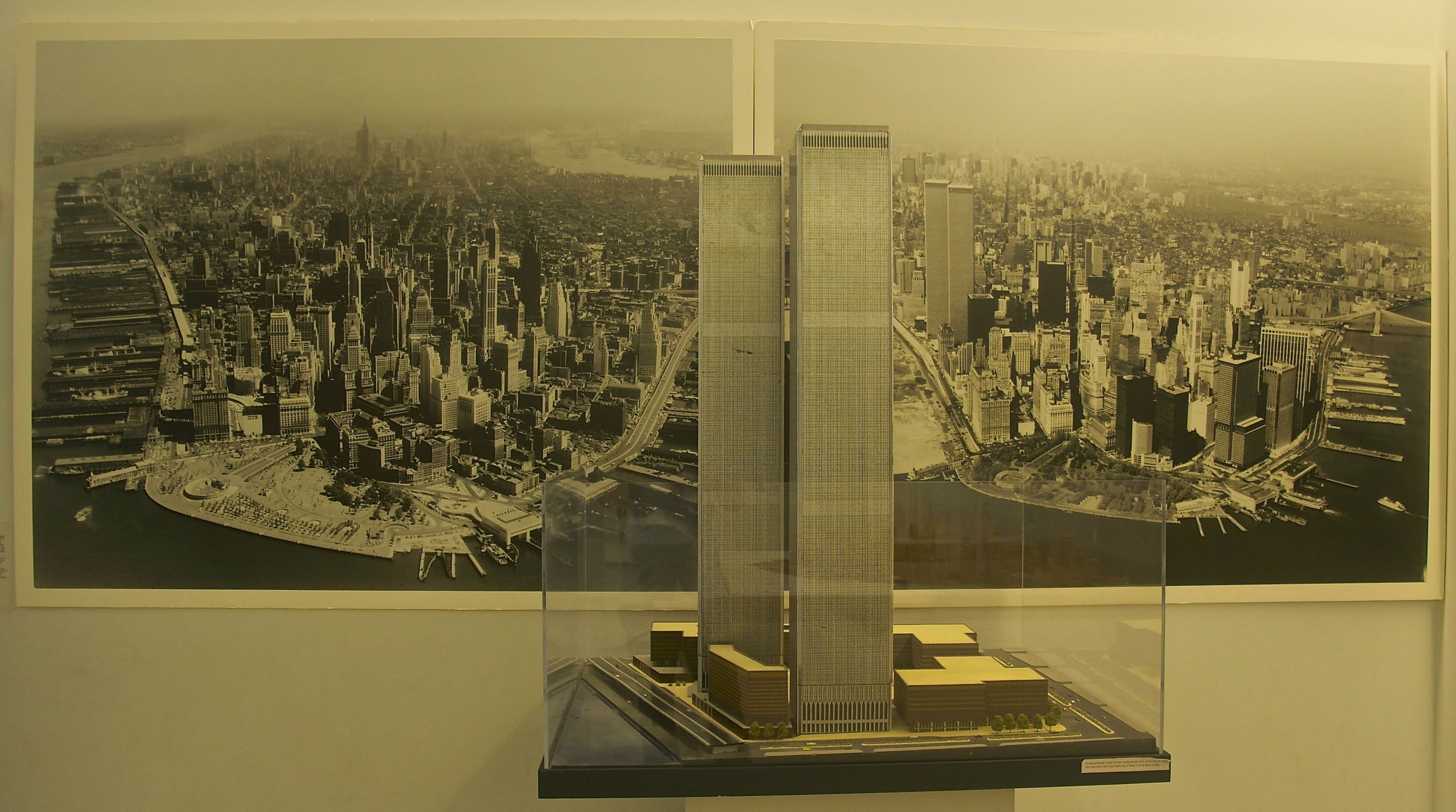 Photos of lower Manhattan serve as a backdrop for models of the Twin Towers at the Skyscraper Museum in New York. The photo on the left shows the area before the towers were built; the second after construction was completed. (Photo: Joseph Kellard/Courtesy Skyscraper Museum).