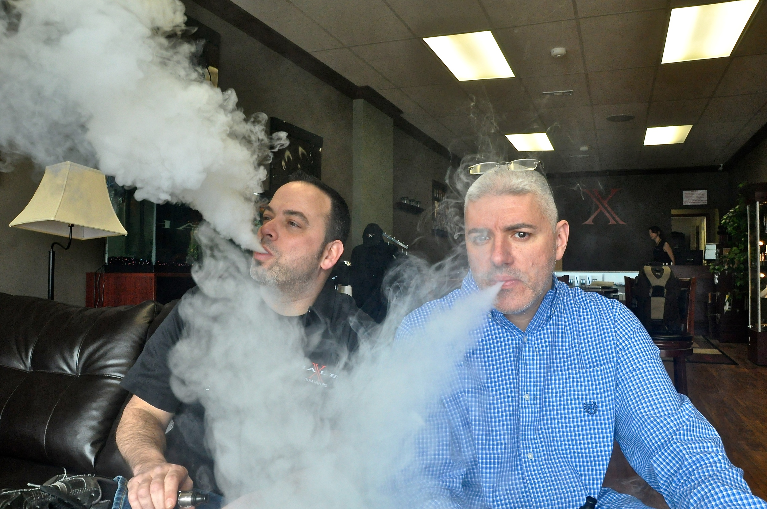 Steve Smith, left, and Douglas Cambria blow clouds of vapor at their e-cigarette shop and lounge, Xhale Custom Vapors in Ronkonkoma, NY. (Photo: Joseph Kellard)