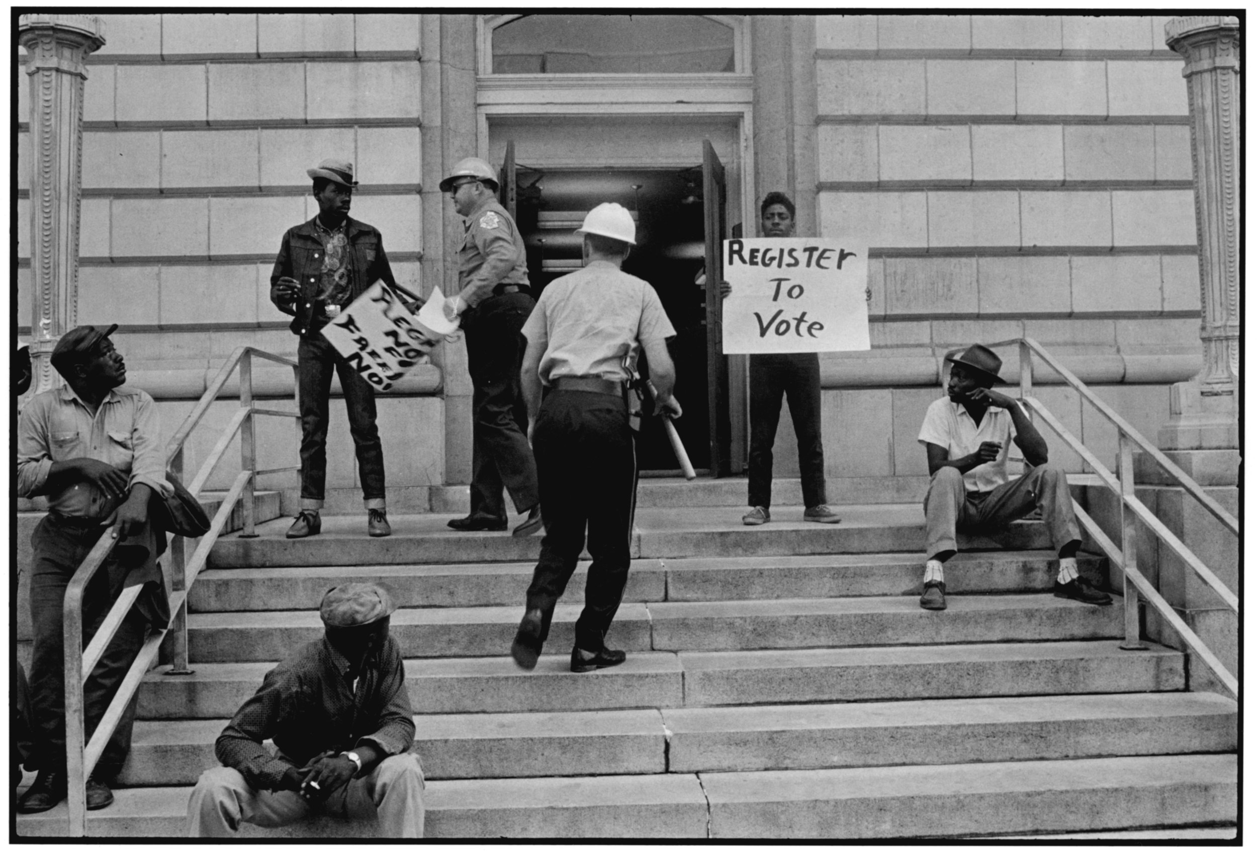 Sheriff Jim Clark arrests two demonstrators who displayed placards on the steps of the federal building in Selma in 1963. (© Danny Lyon, New York & Magnum Photos, New York / Courtesy Edwynn Houk Gallery, New York.)