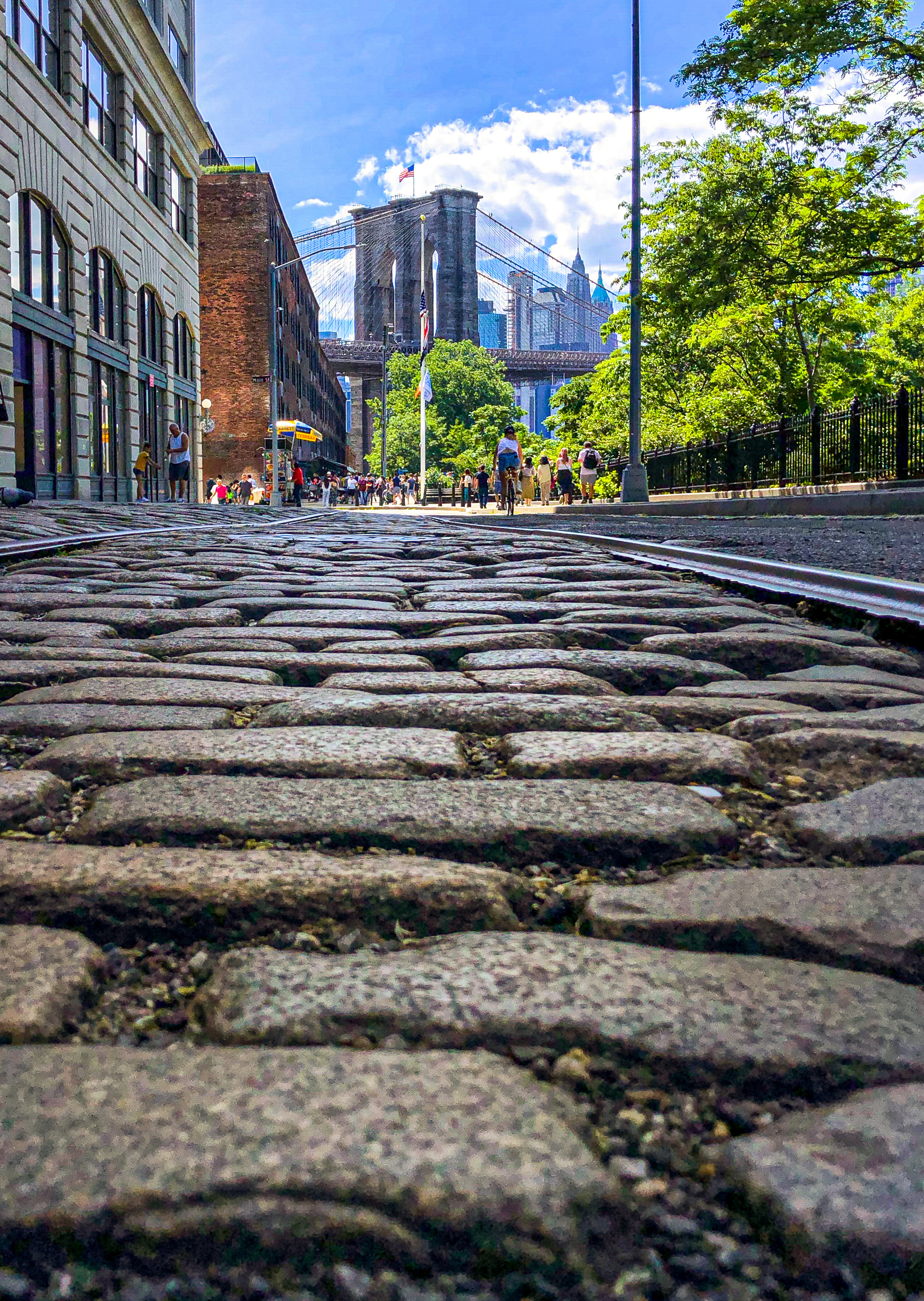 I returned to Plymouth Street in Brooklyn, which aligns with the bridge's tower, to retake this perspective that brings viewers into the crannies of its cobblestones. I wanted to capture the sky more clearly and got an assist from clouds.