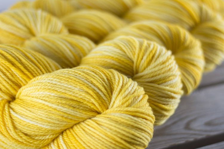 These skeins of  Columbia Aran in Duckling  show subtle differences in value: the skein in the foreground is slightly darker than the skein behind it.