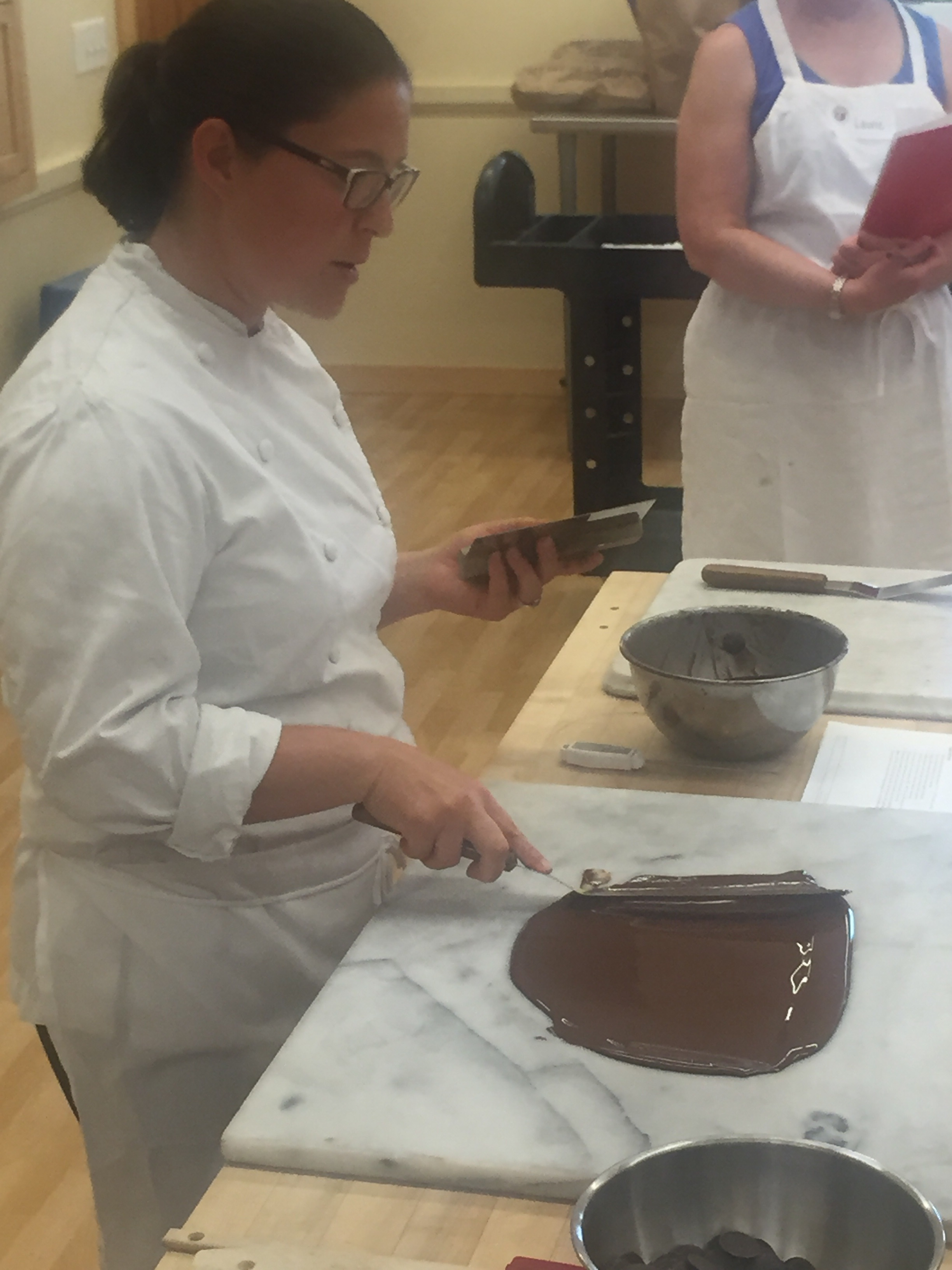 Our instructor, Melanie, tempering chocolate via the table method.