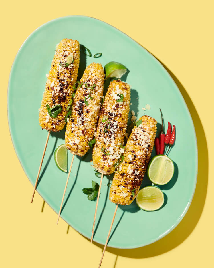 credits: photo- jenna gang, food styling- joanna keohane, prop styling- rebecca crea  description: conceptual still life food photograph of grilled corn on a bright blue plate.