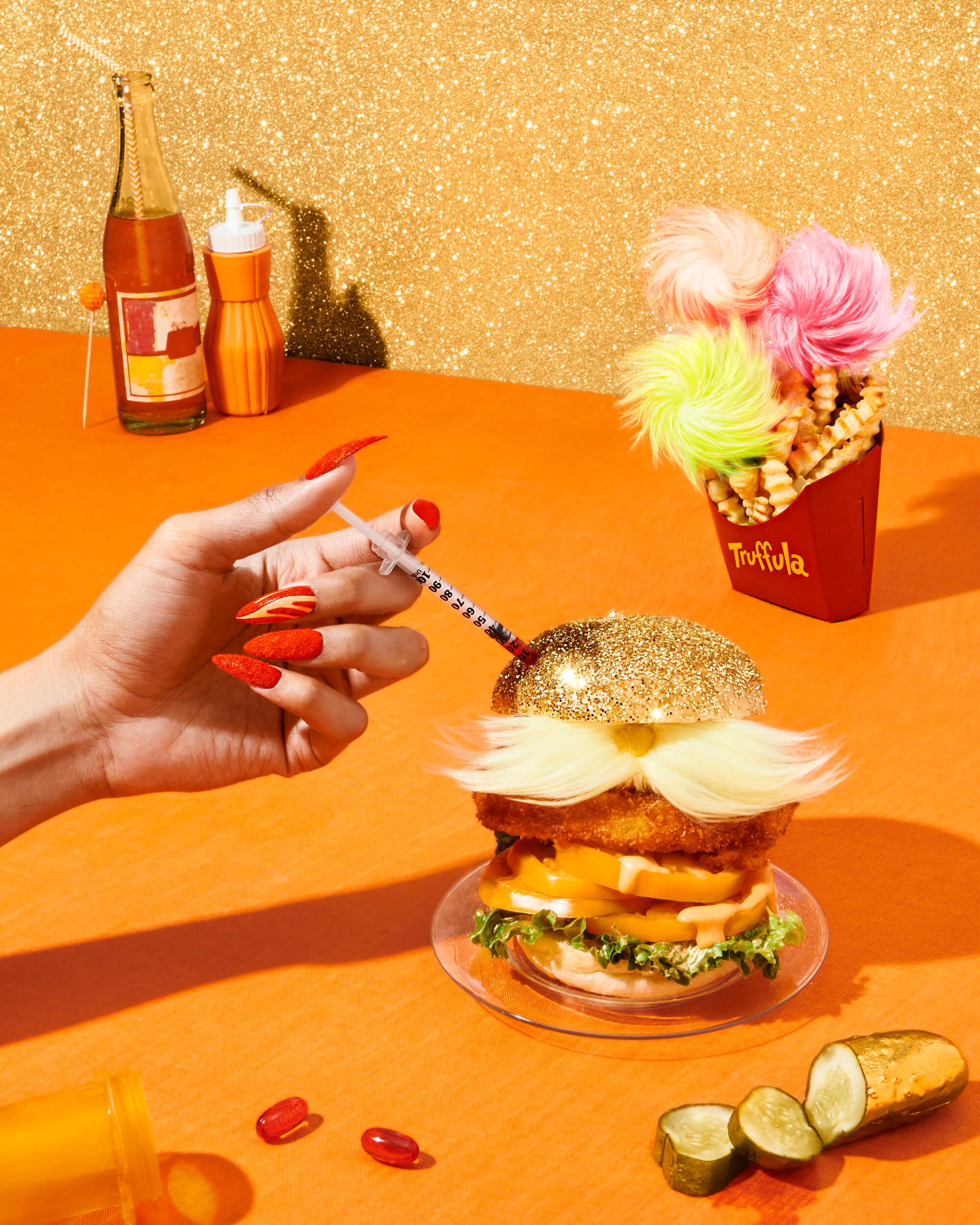 "credits: photo- jenna gang, creative direction- edward yeung, prop styling- anna lemi, food styling- ali nardi, manicure- ada yeung, model- idriss bozhilov  description: onceptual food photograph of ""Lorax Burger"" from Dr. Seuss."