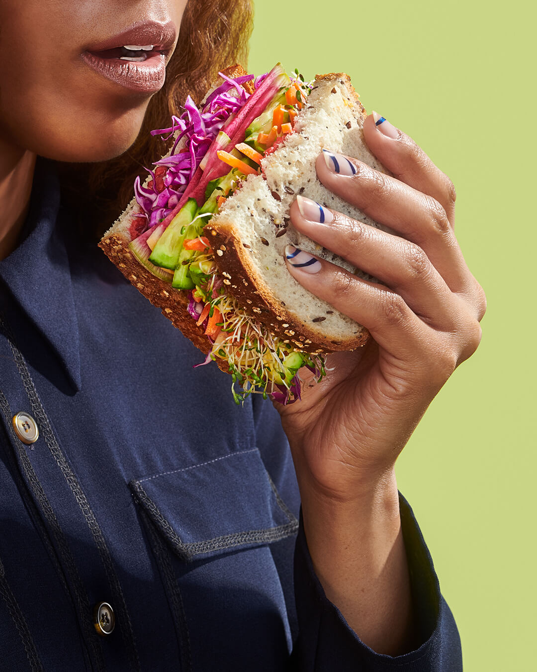 credits: photo- jenna gang, food styling- jen beauchesne, clothing- ross mcCallum, nail design- Ada Yeung, nail tech- michelle sun.  description: conceptual still life of model eating a veggie sandwich.