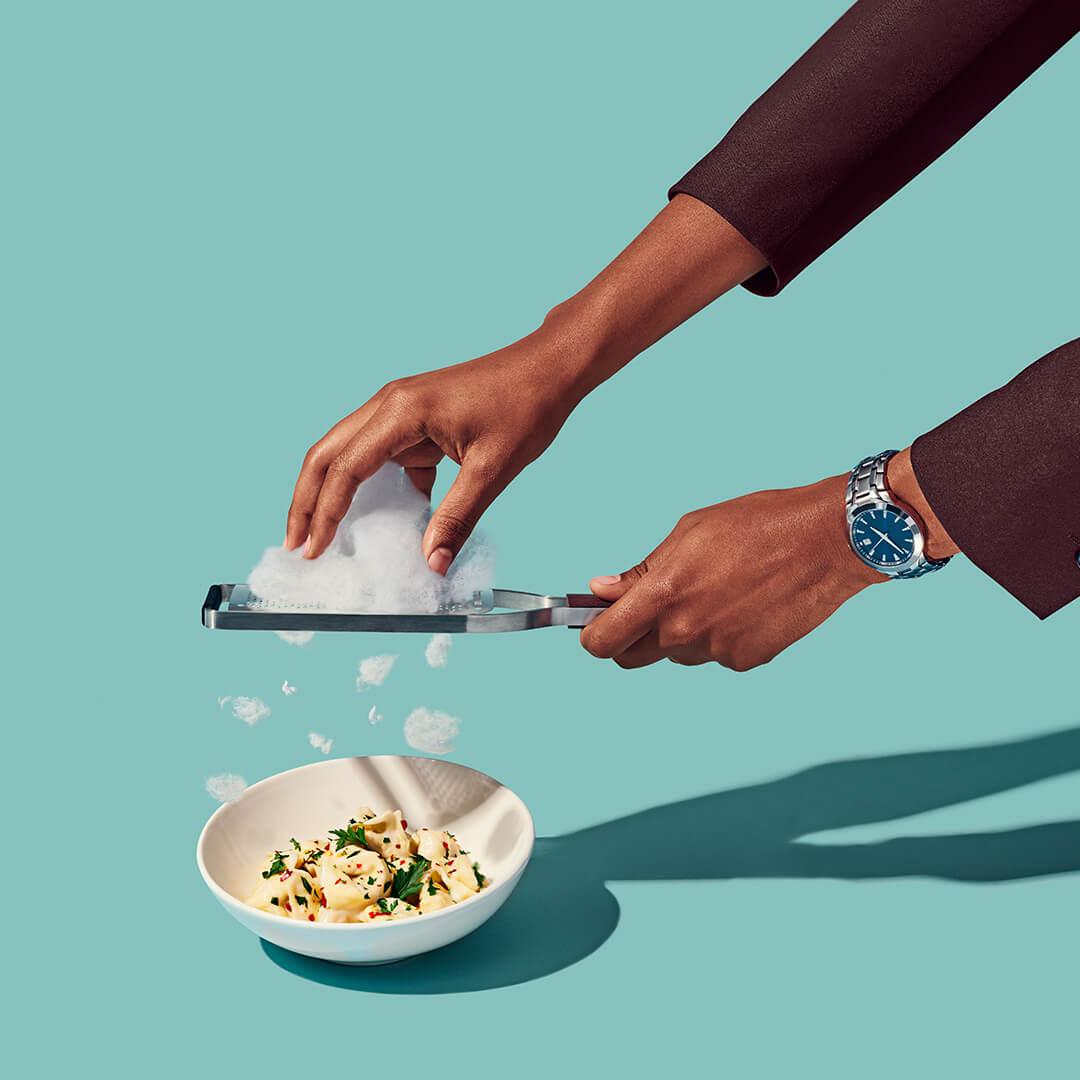client: virgin atlantic  credits: photo- jenna gang, food styling- ali nardi  description: conceptual still life photograph of modeling shaving cloud parmesan on pasta.
